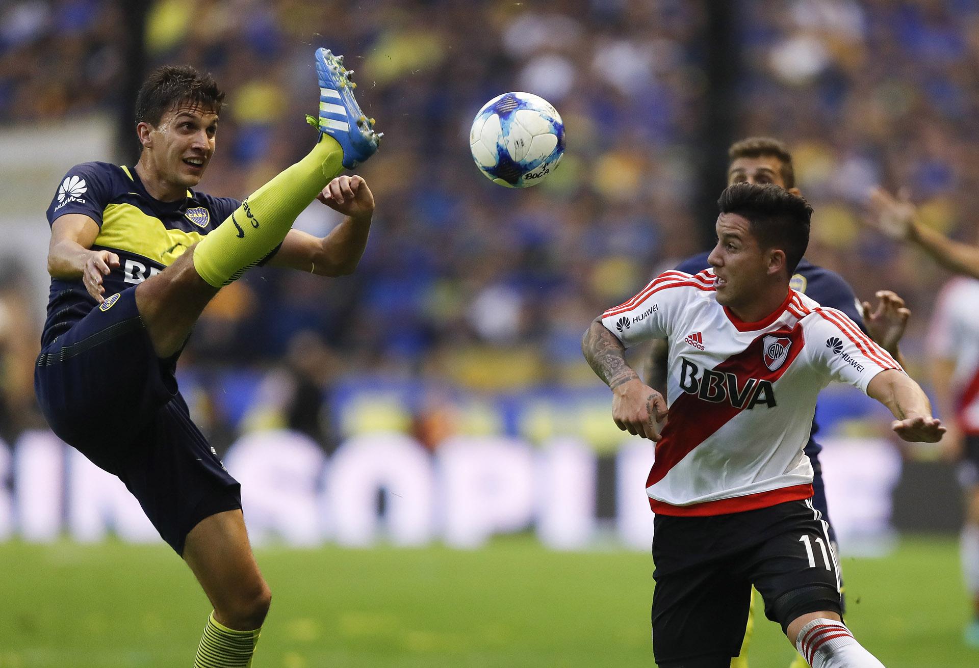 Santiago Vergini, con la pierna arriba, disputa el balón con Sebastián Driussi