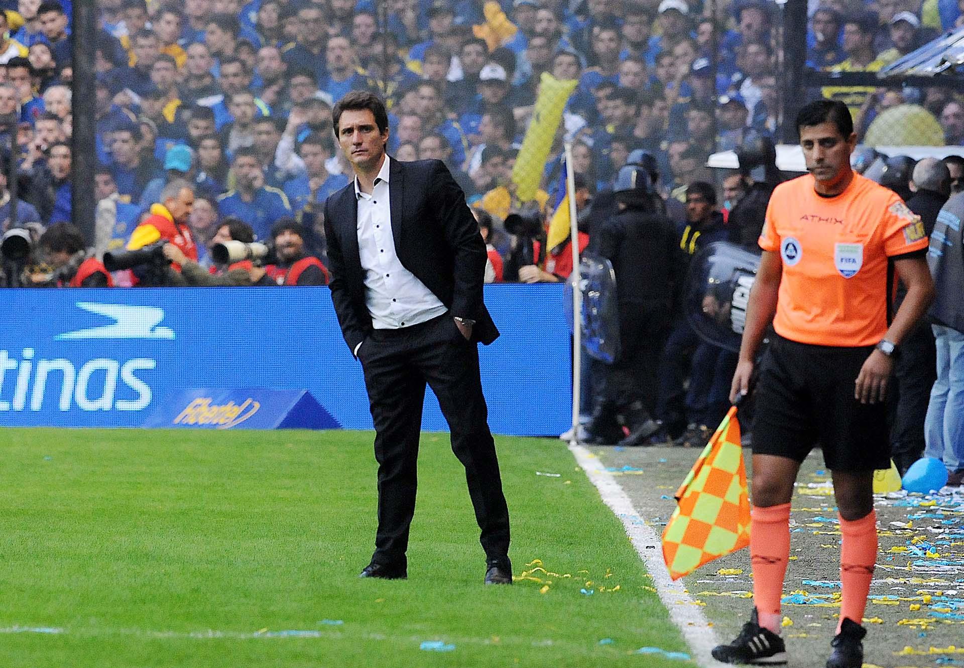 Guillermo Barros Schelotto observa una jugada desde el banco de suplentes