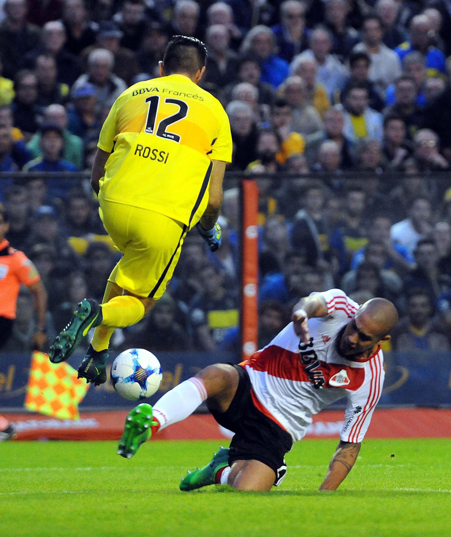 En el aire, el arquero xeneize Agustín Rossi bloquea una pelota