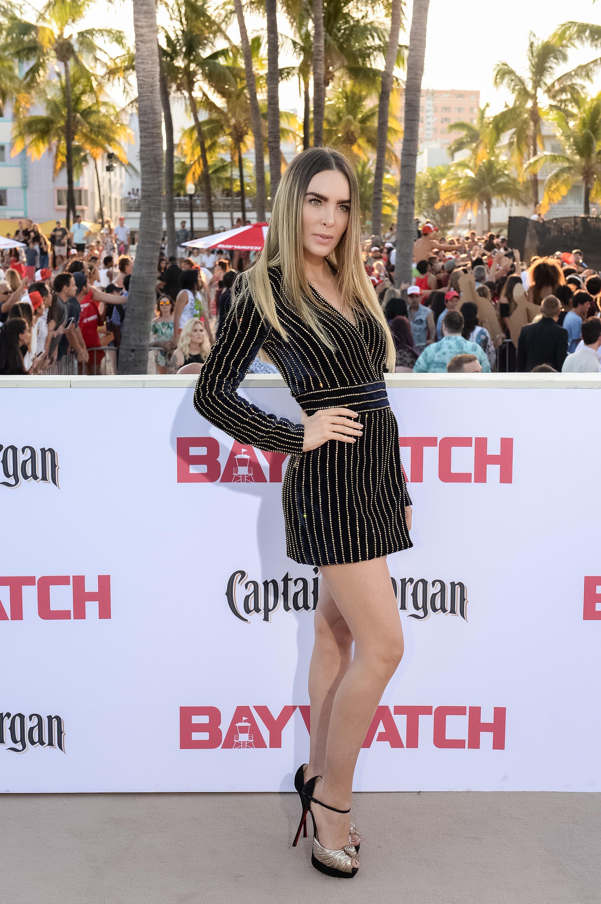 Belinda con un escotado vestido negro con rayas oro