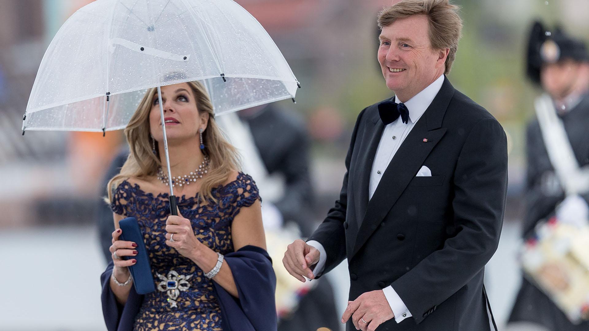 Al igual que el resto de los invitados, la reina de Holanda se refugió de la llovizna bajo un paraguas transparente