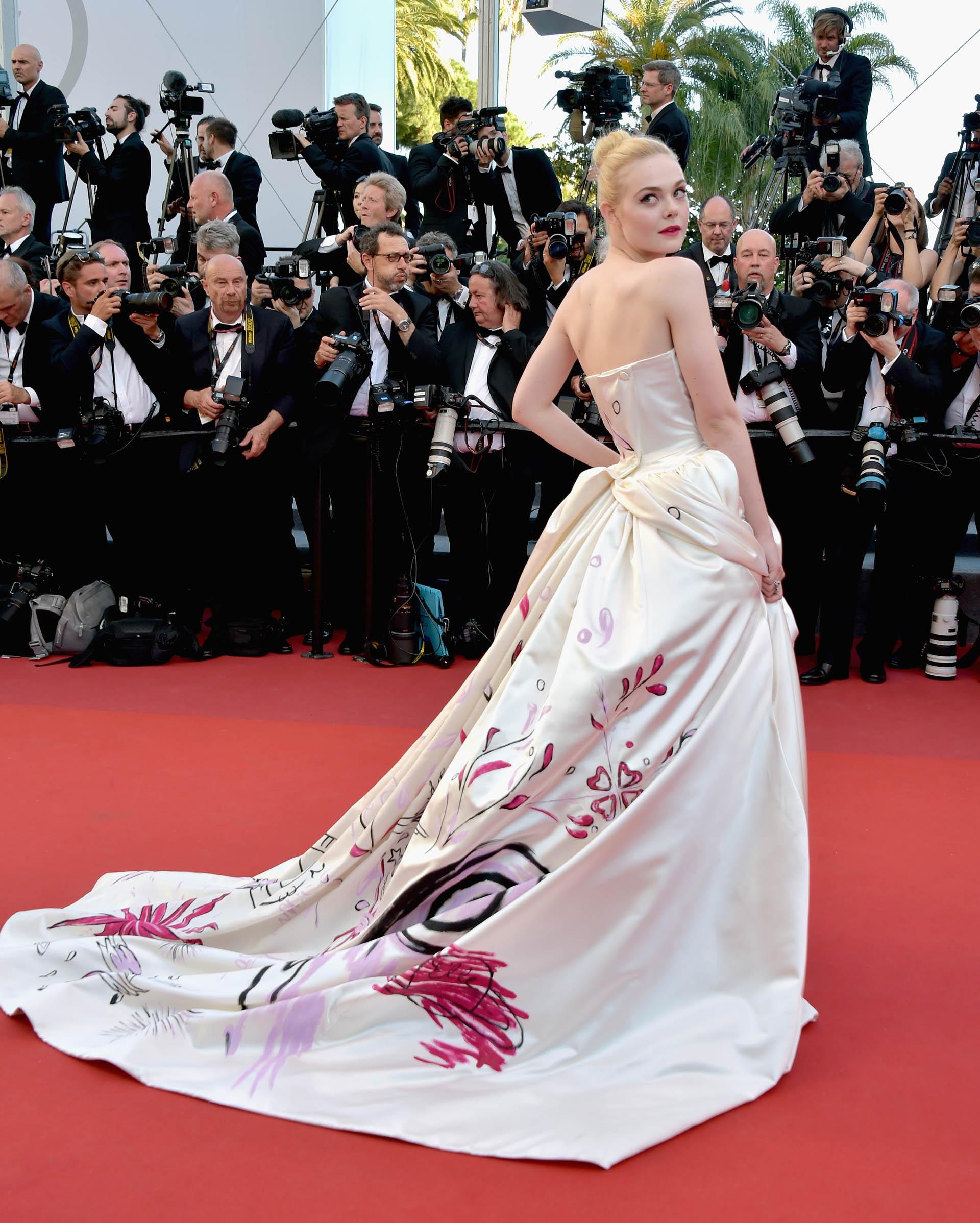 Elle Fanning deslumbró en esta edición del festival con un vestido tiza con un diseño único en la falda firmado por Vivienne Westwood. Completó su look con un maquillaje cat eye y labios rosa mate (Pascal Le Segretain/Getty Images)