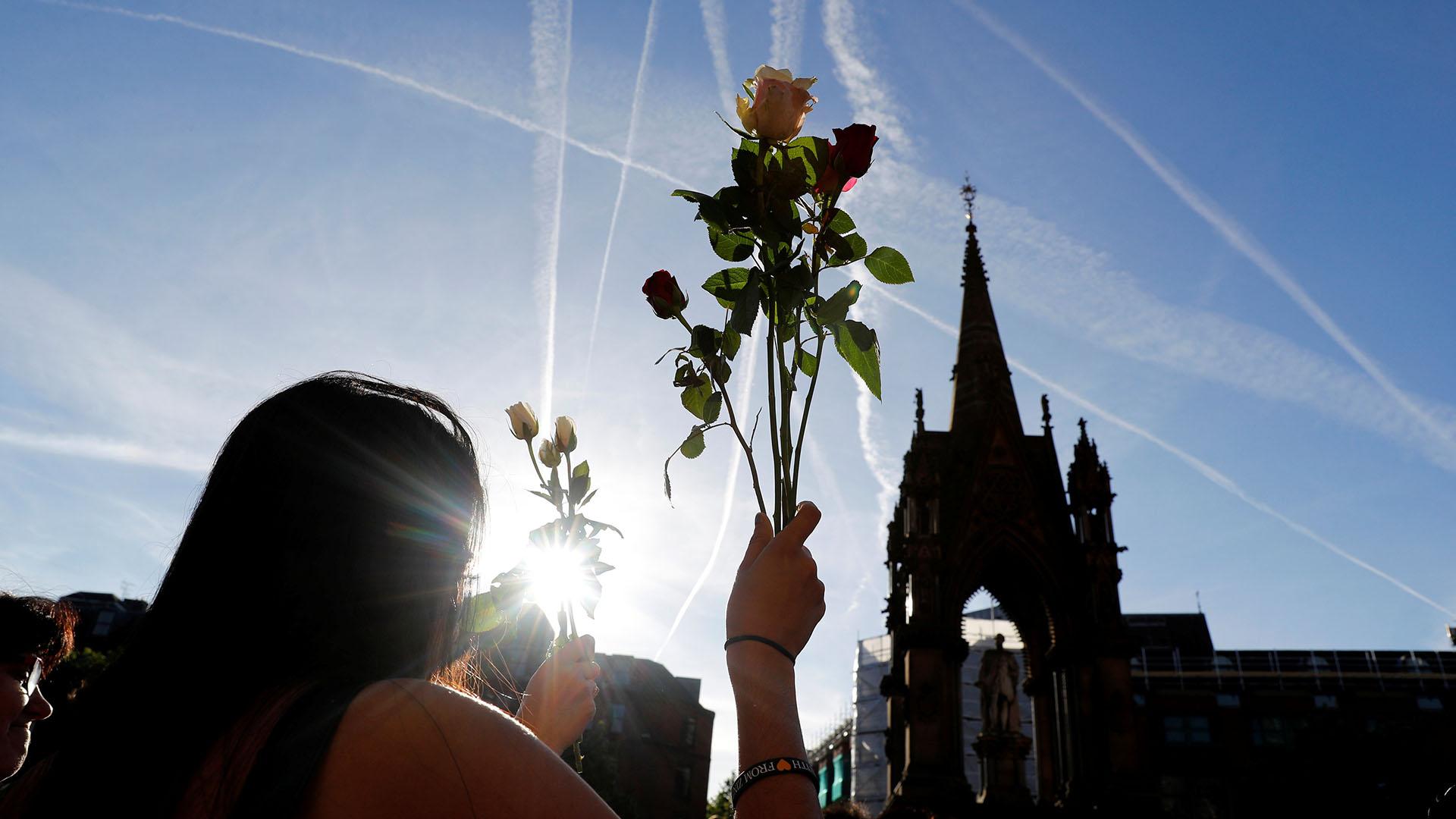 Una mujer sostiene un ramo de flores en medio de la vigilia (REUTERS)