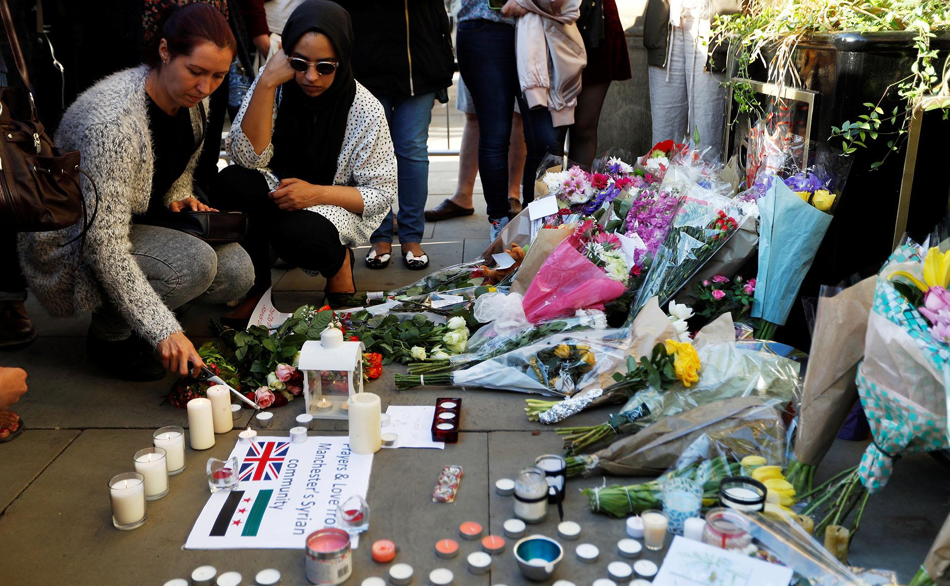 Un grupo de mujeres prende velas en memoria de las víctimas del atentado (REUTERS)