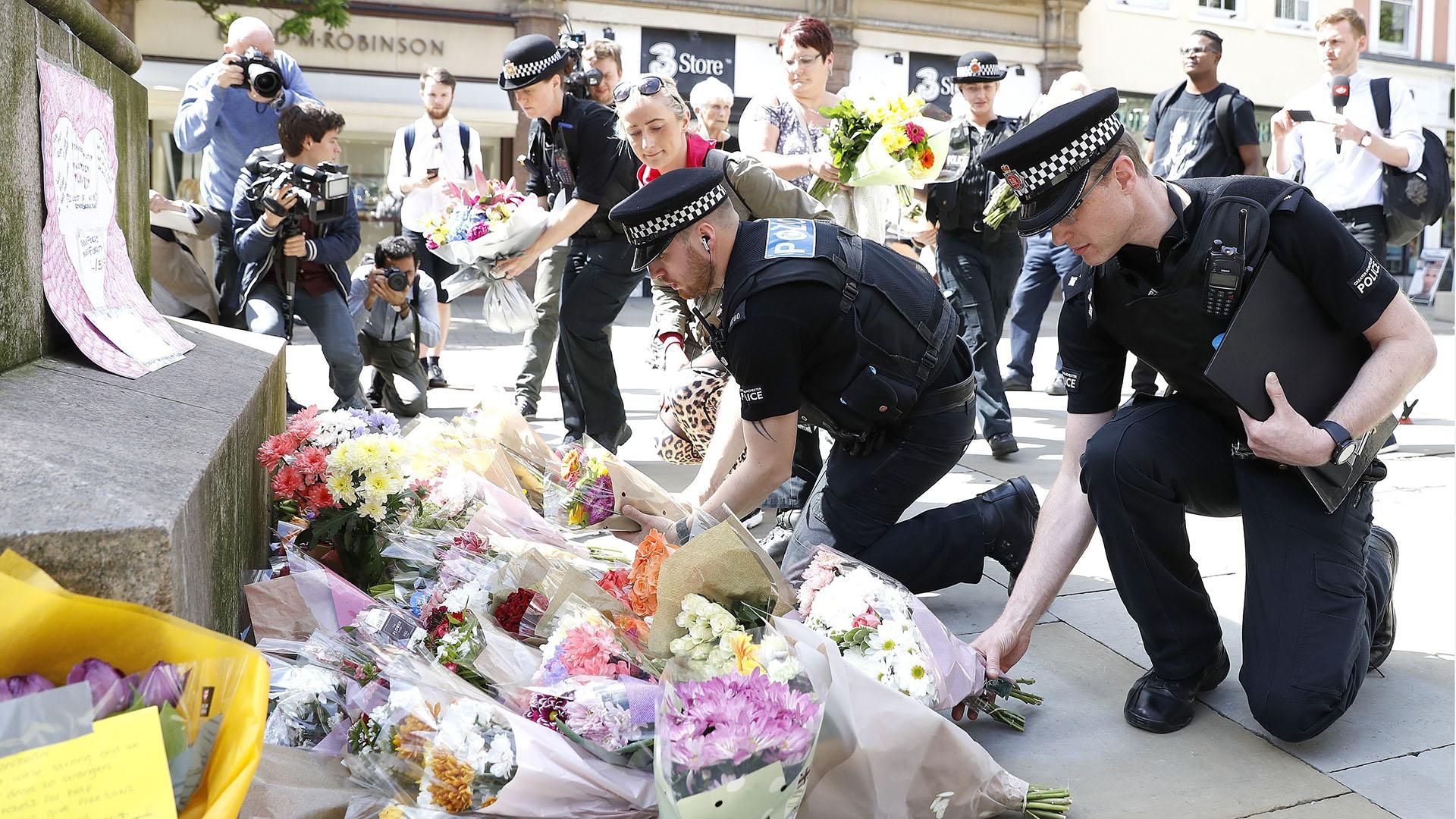Policías británicos dejan flores en el centro de Manchester (AP)