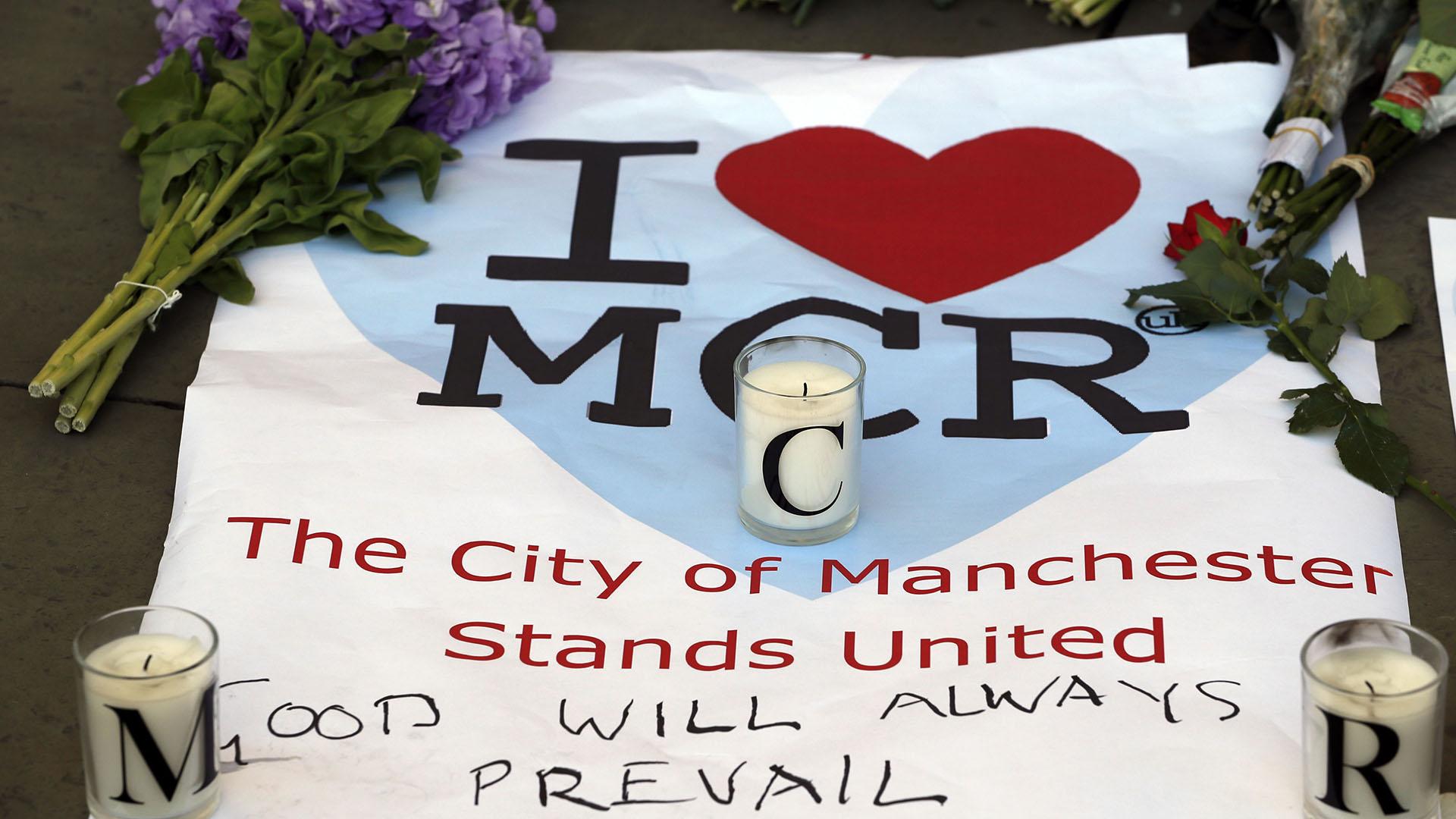 """""""La ciudad de Manchester permanece unida"""", se puede leer en una bandera tendida sobre el piso con flores y velas (AP)"""