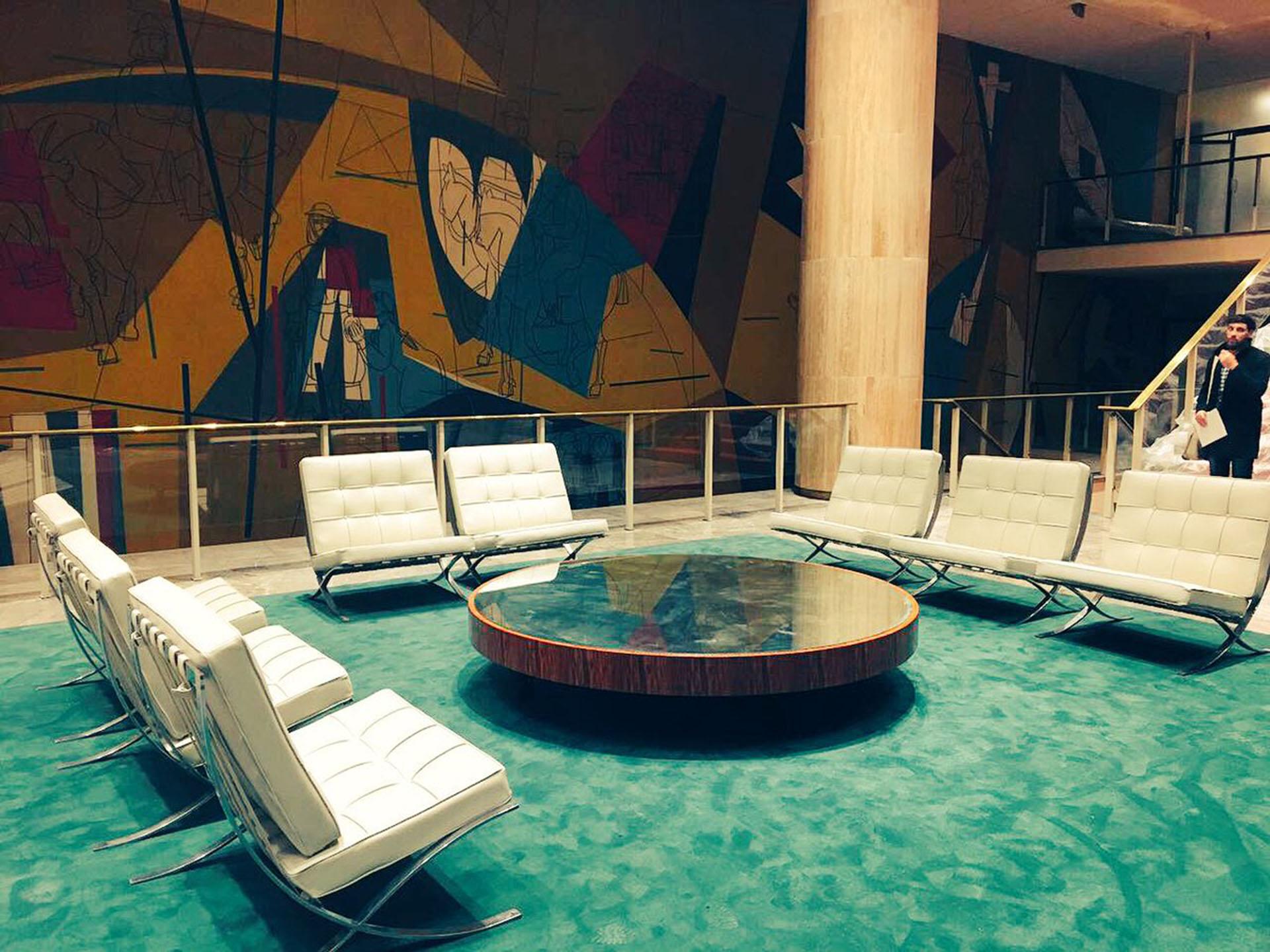 """De fondo, el mural del maestro Seoane y en el centro una mesa espejo rodeada de ocho sillones """"Barcelona"""""""