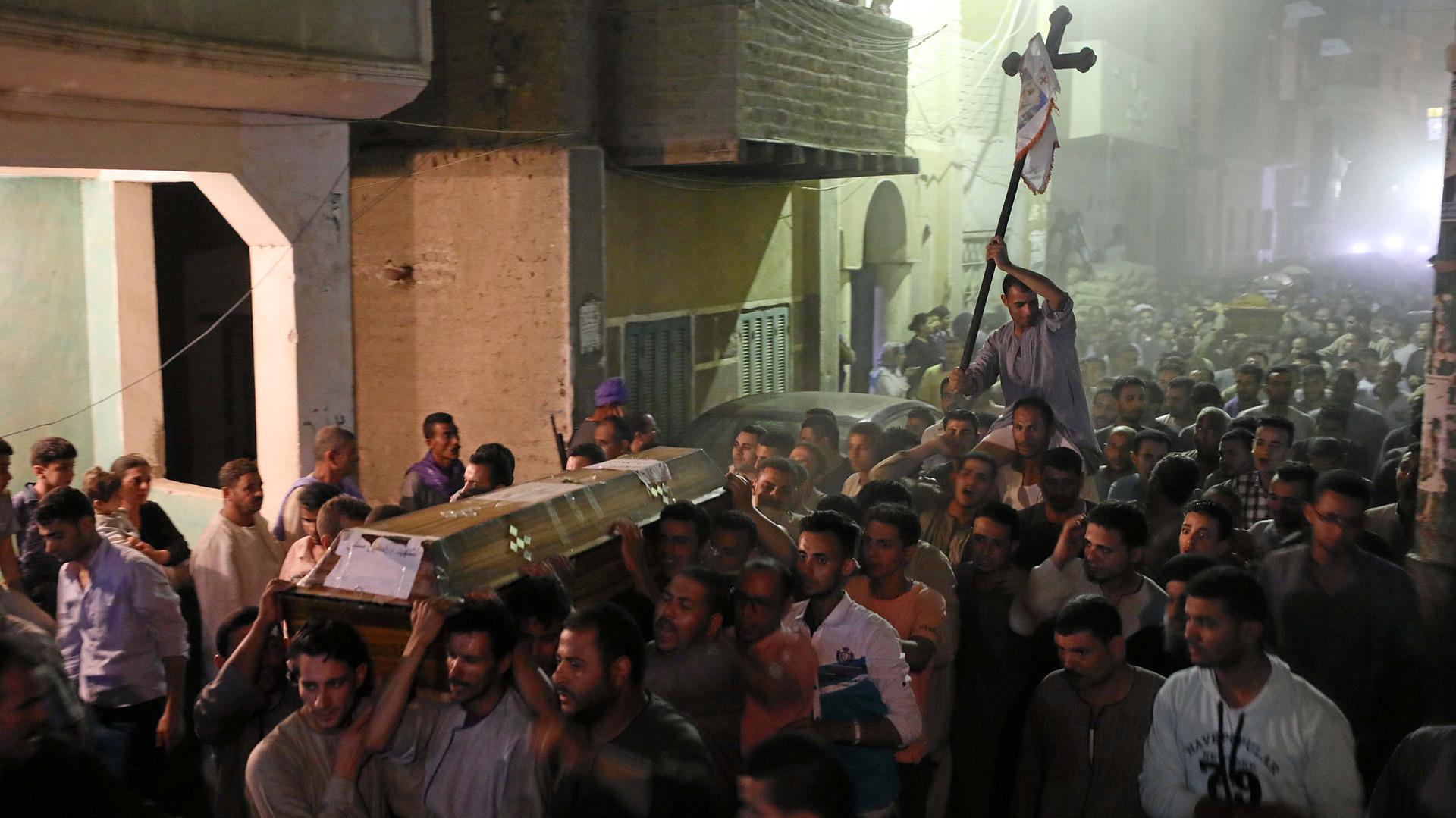 Un grupo de cristianos llevando los féretros de los fallecidos durante el ataque