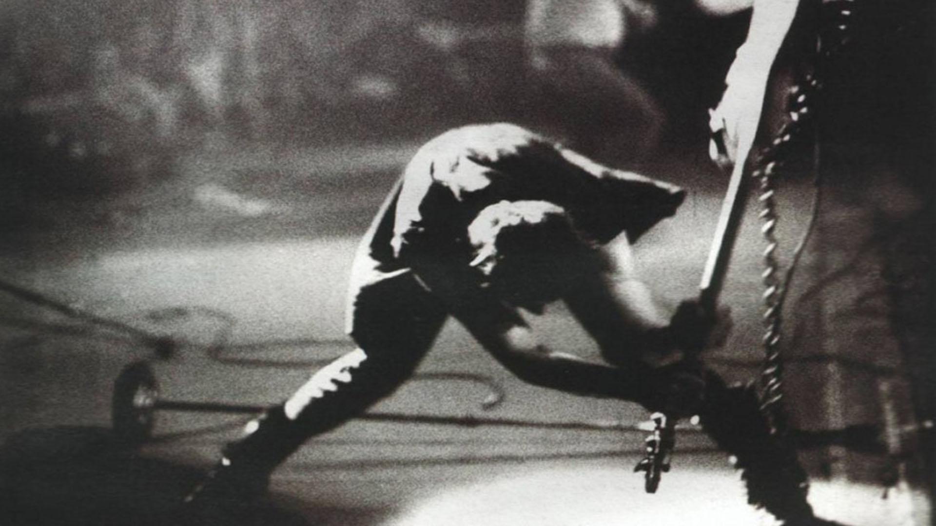 Paul Simonon de The Clash golpeando su bajo contra el escenario en un show