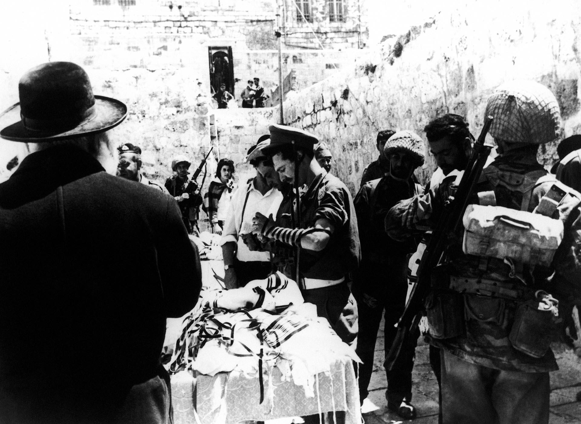 8 de junio de 1967. Judíos ortodoxos y soldados rezan ante el Muro de los Lamentos en Jerusalén, un día después de su captura de manos de los jordanos. (AP)