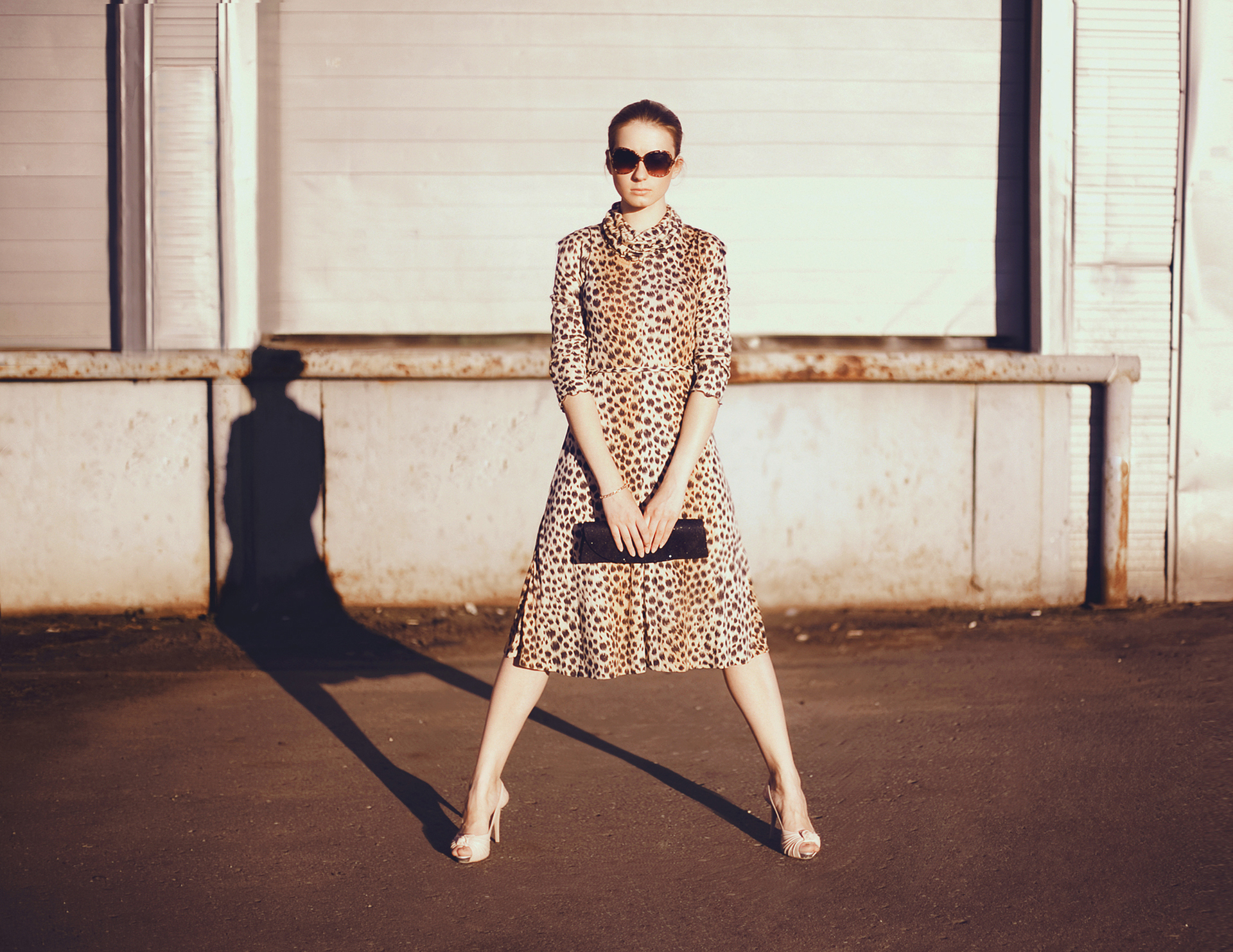 Stylish woman in a leopard dress, glasses and bag in the ghetto evening, street fashion.