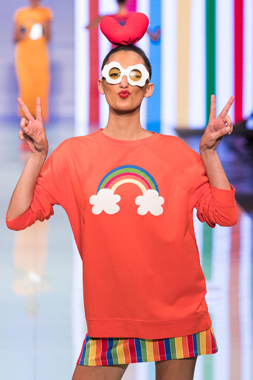 Con anteojos llamativos en forma de flor, el buzo coral con arcoiris y debajo un mini vestido multicolor.