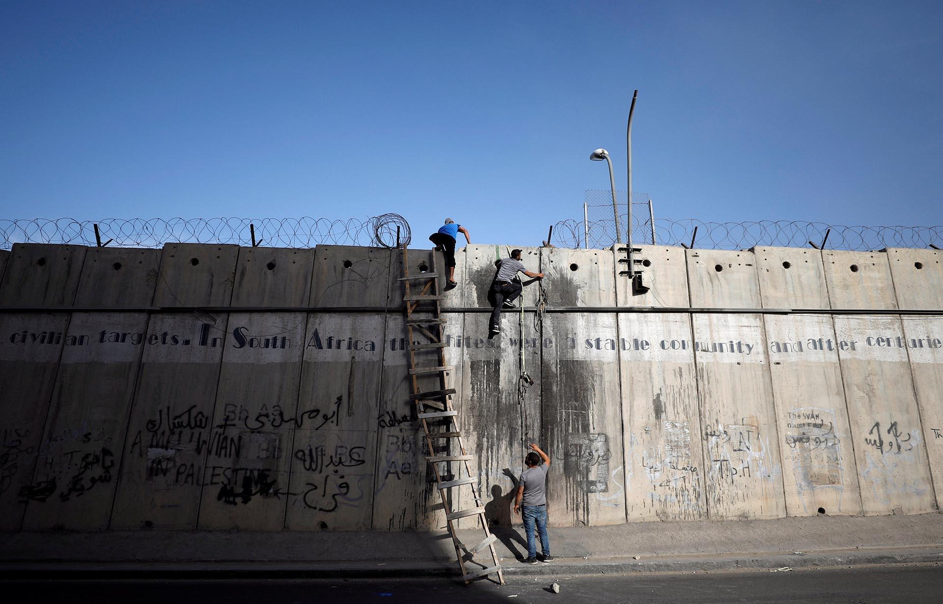 Palestinos escalan una sección de la controvertida barrera israelí mientras tratan de hacer su camino para asistir a las oraciones del Ramadán en la mezquita de Jerusalén, cerca de Ramallah