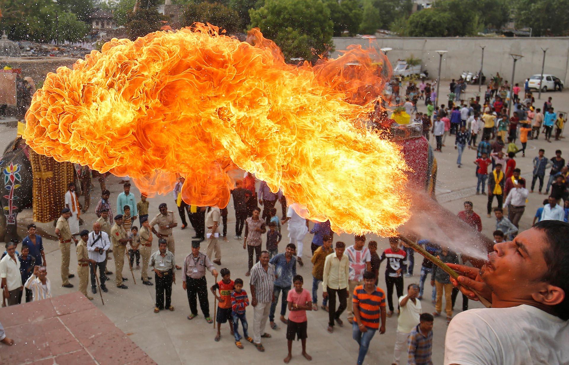 Un devoto hindú realiza un truco con fuego durante la procesión Jal Yatra antes de la anual Rath Yatra que se celebrará el 25 de junio en Ahmedabad, India