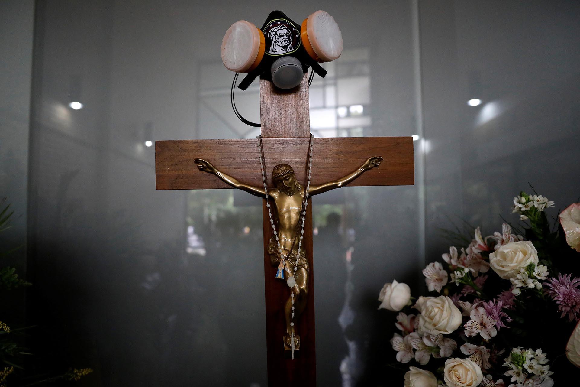 Una máscara antigas cuelga de un crucifijo sobre un ataúd en el funeral de Neomar Lander, asesinado por la policía chavista durante una protesta contra el gobierno de Nicolás Maduro