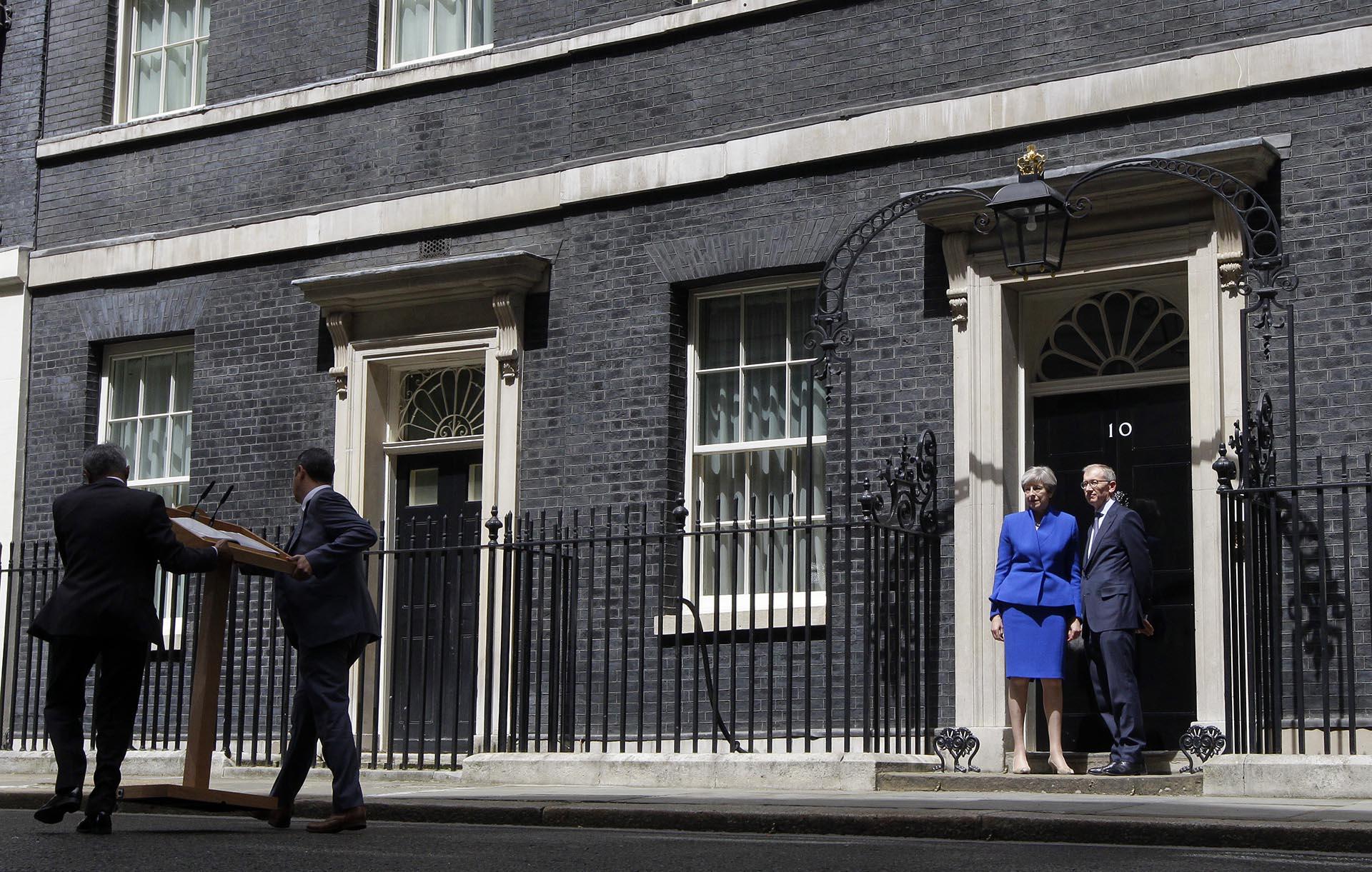 La premier británica Theresa May y su esposo Philip en la puerta de Downing Street tras dirigirse a la prensa este luego de la audiencia con la reina Isabel II en el Palacio de Buckingham
