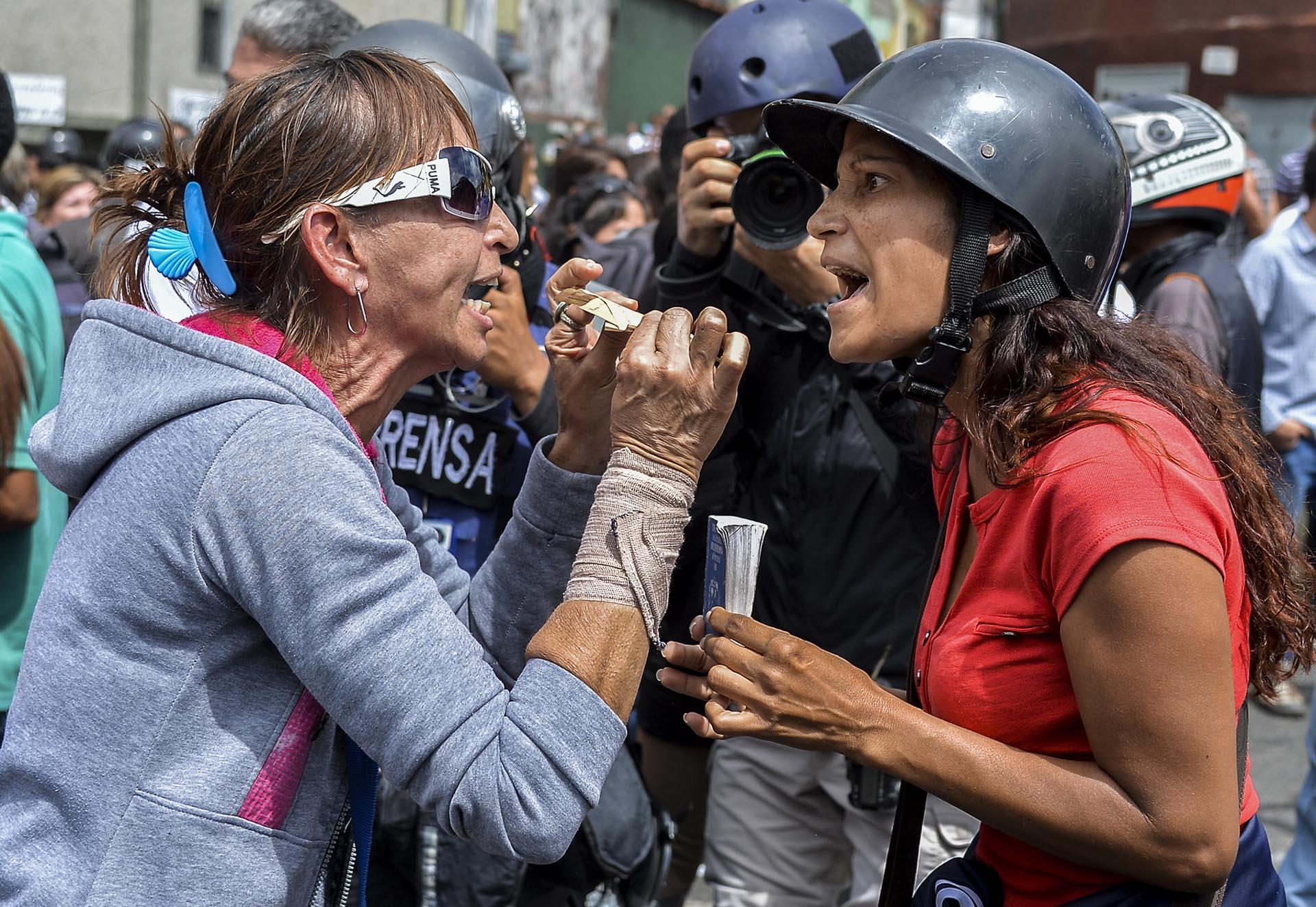 Una partidaria del gobierno de Nicolás Maduro y una manifestante de la oposición discuten frente a la Corte Suprema de Justicia (AFP)