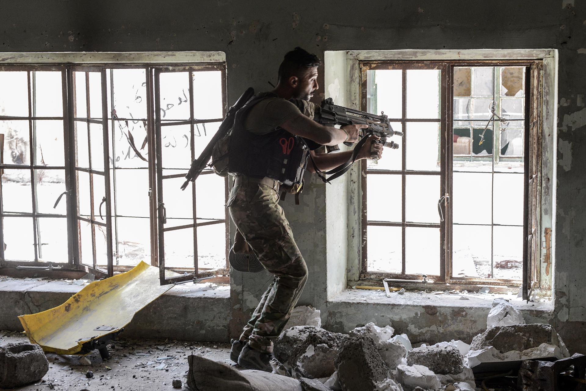 Un soldado de las tropas de élite iraquíes apunta desde un edificio contra los terroristas del Estado Islámico en el distrito de Al Shifa en la parte occidental de Mosul (AFP)