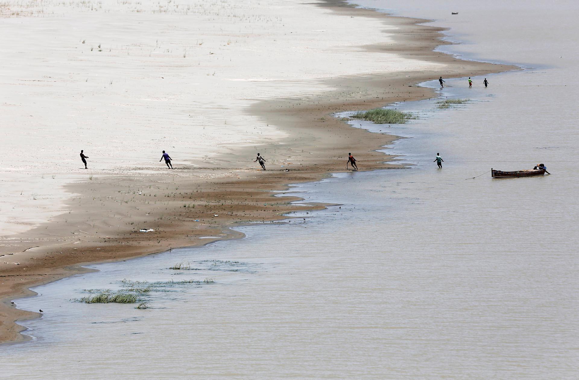 Pescadores tiran de una red en el río Indus, en Hyderabad, Pakistán (Reuters)