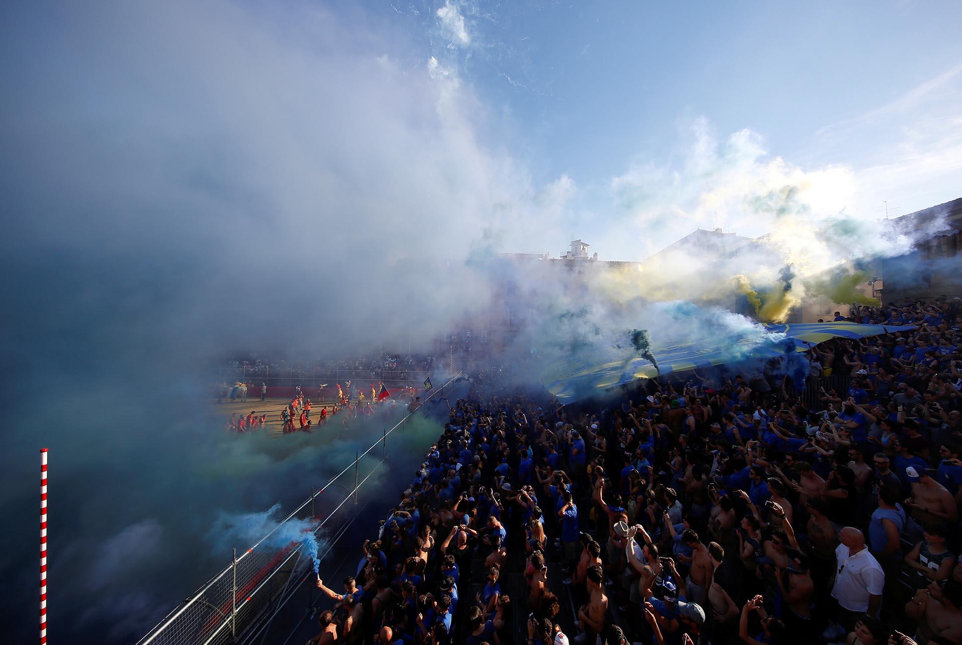 """Fanáticos del equipo italiano Santa Croce celebran con bengalas y una gran bandera luego de un partido de """"Calcio Fiorentino"""", un estilo primitivo del fútbol convencional (Reuters)"""