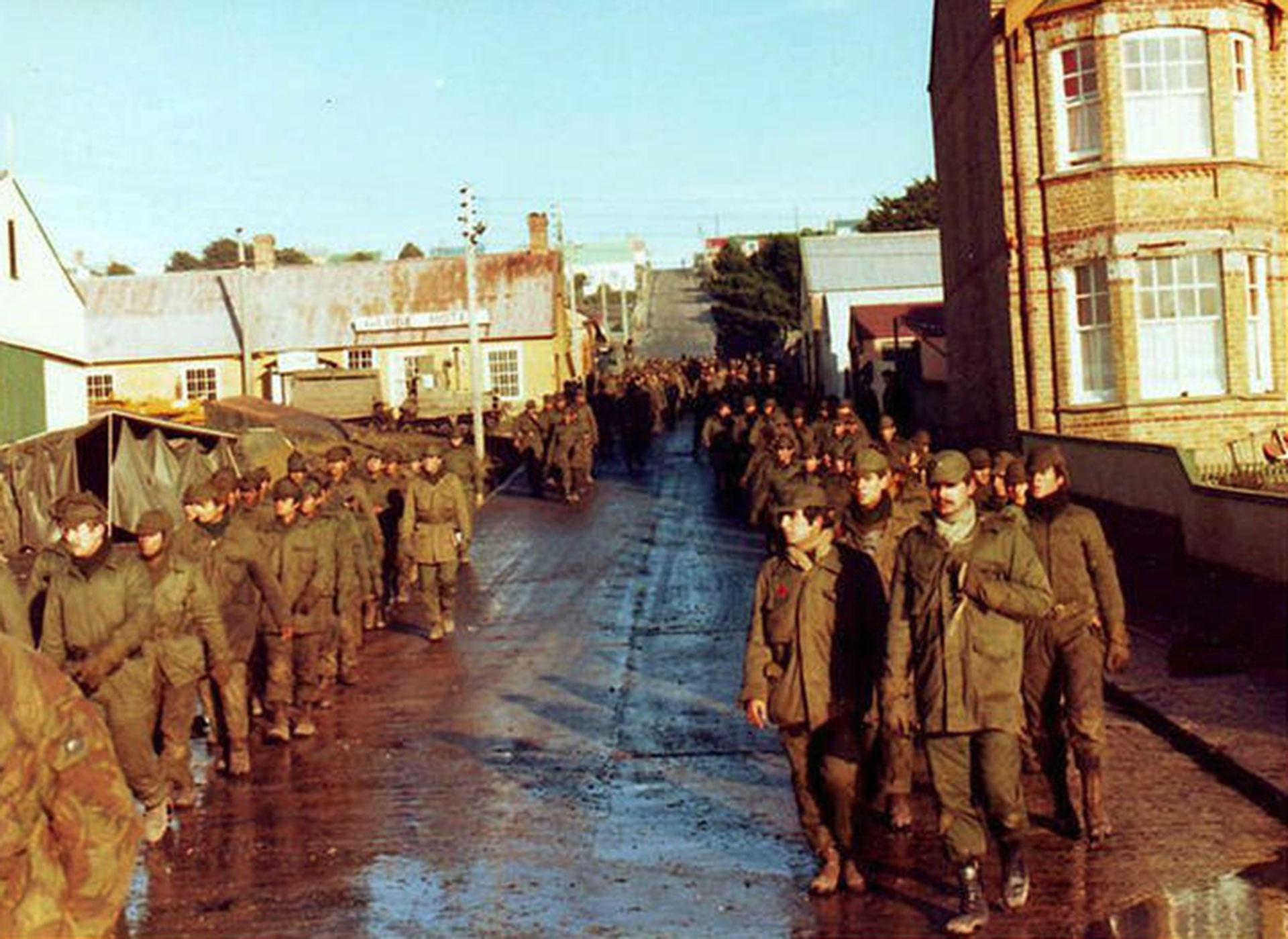 Bajo los obuses, riadas de soldados confluyeron sobre Puerto Argentino, conla idea de que los ingleses no bombardearían la población civil de la capital de las islas