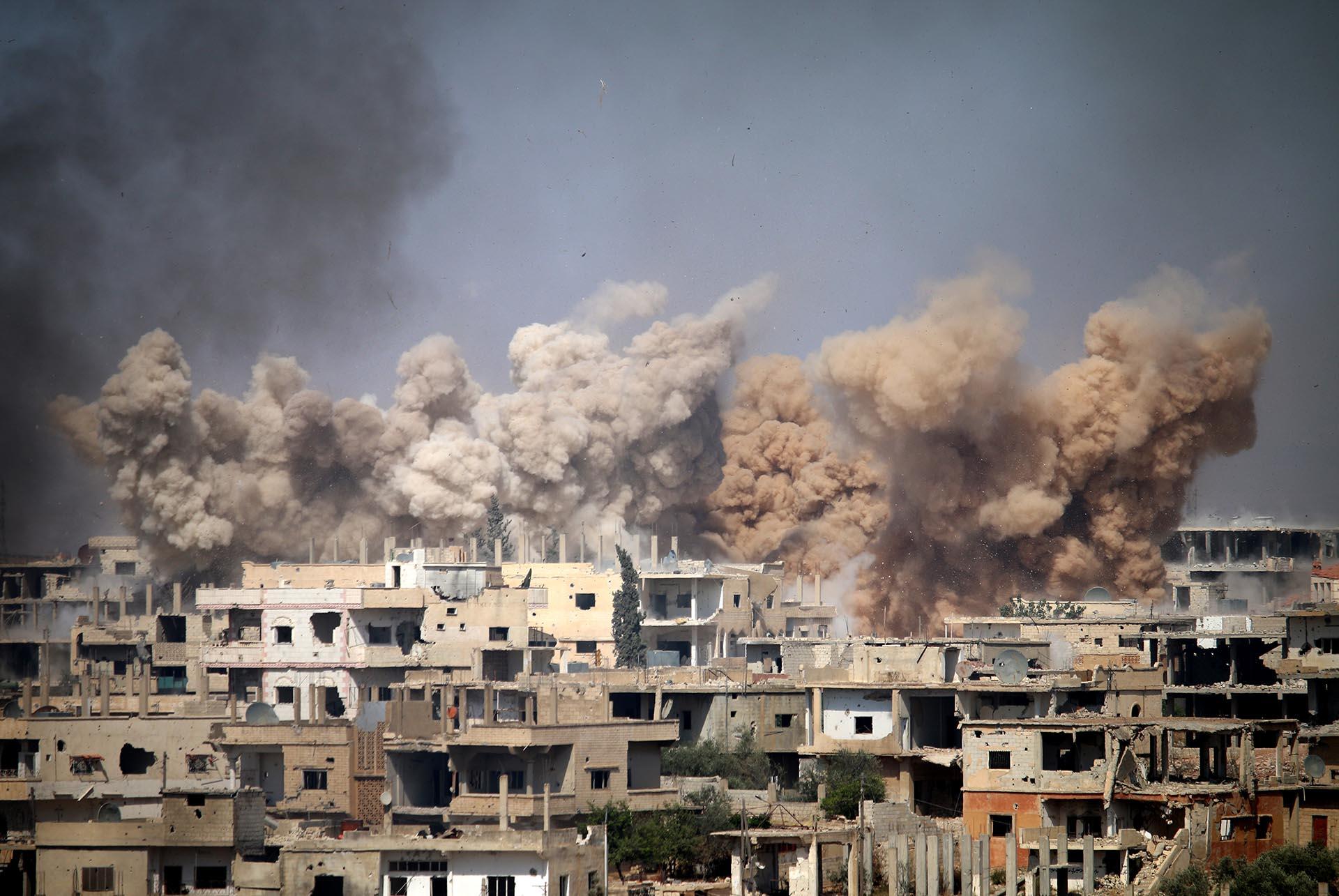 El humo entre los edificios después de un ataque aéreo en una área controlada por los rebeldes en la ciudad siria de Daraa