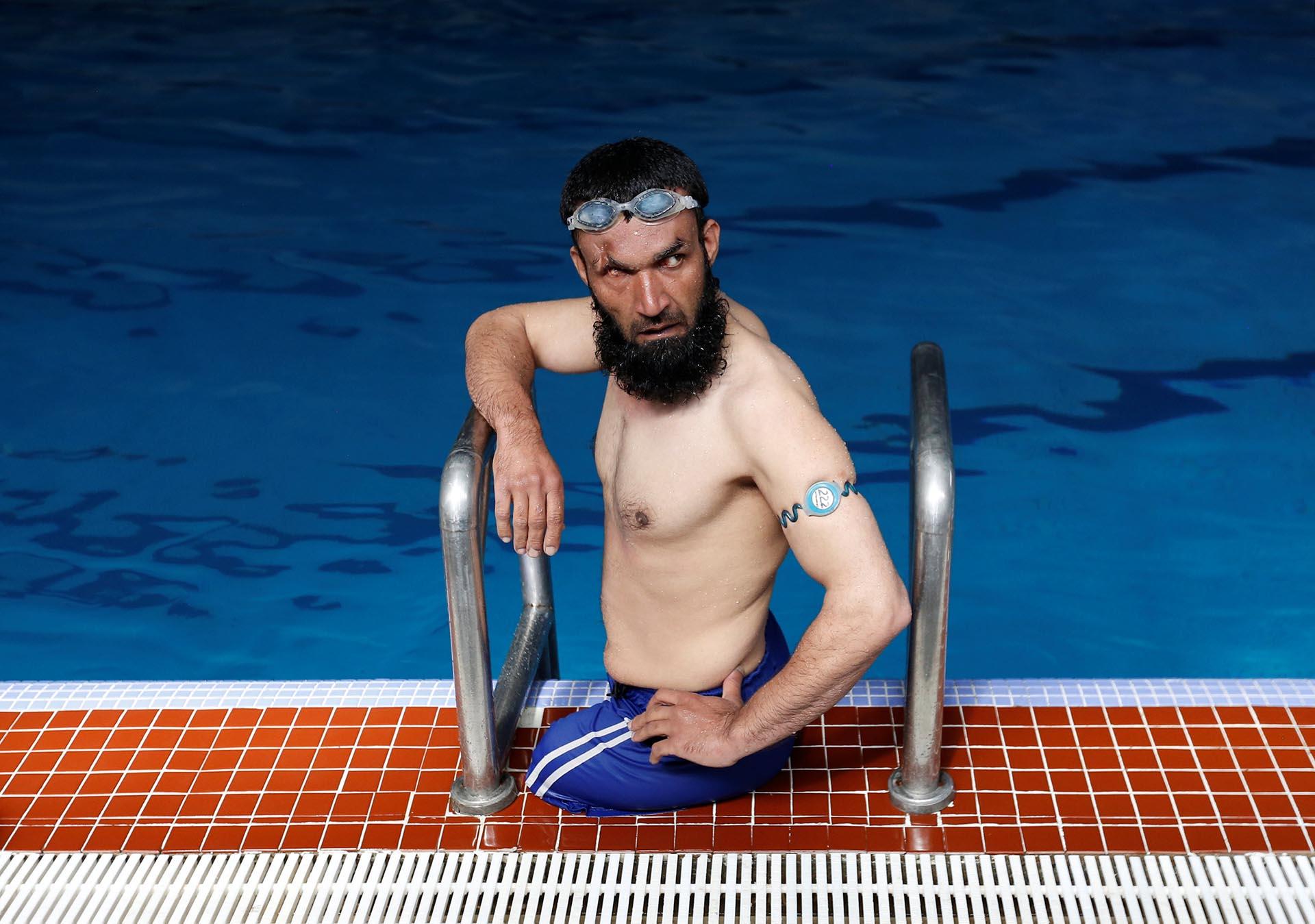 Khan Agha, de 28 años, se sienta al borde de una piscina durante su práctica en Kabul, Afganistán