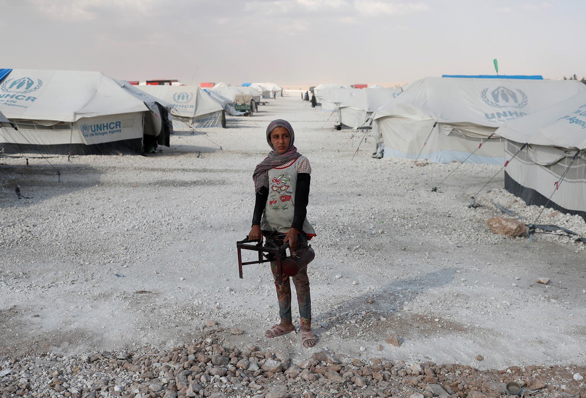Una adolescente sostiene una cocina en un campamento para personas desplazadas de sus hogares en Ain Issa, Siria, por la violencia del Estado Islámico