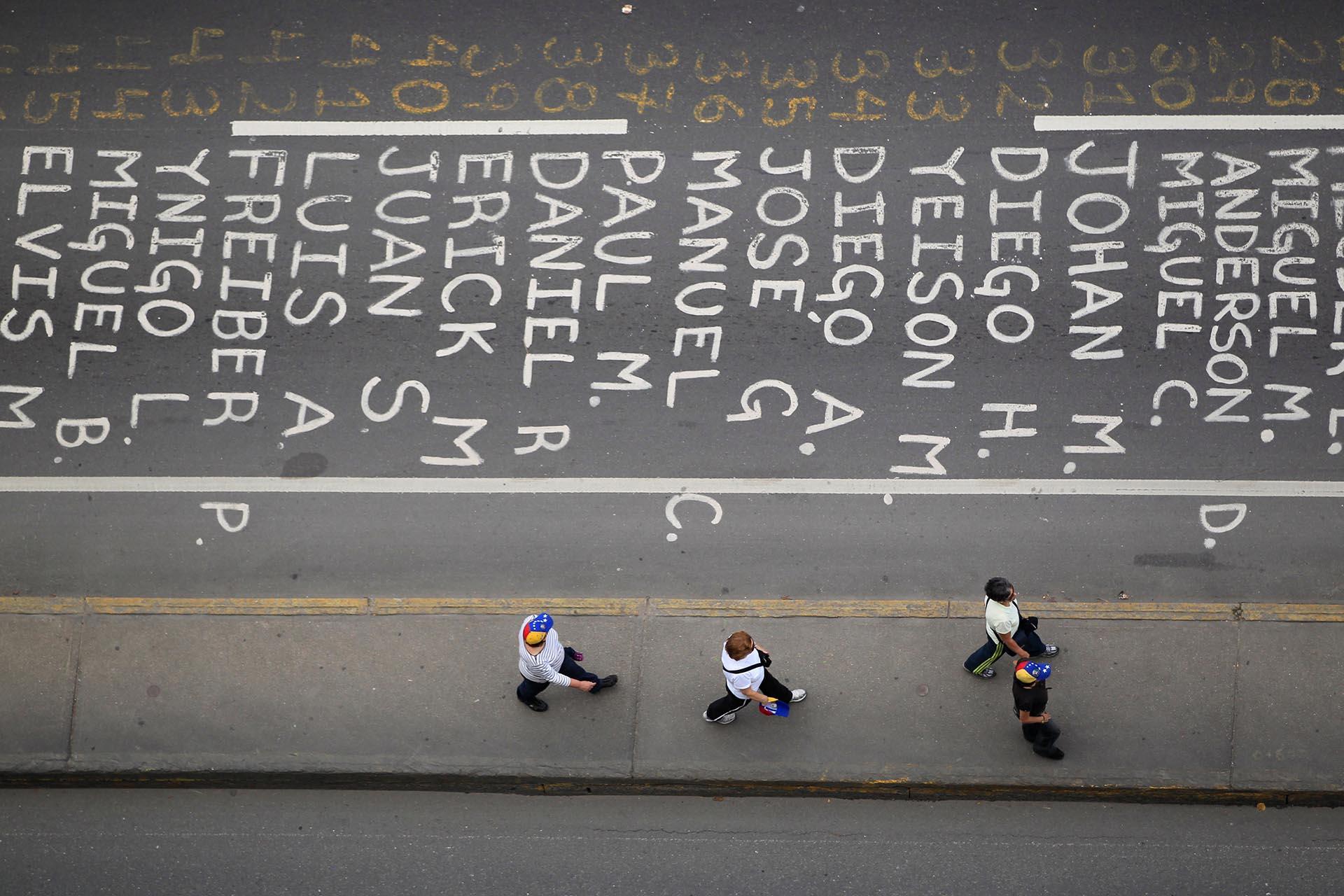 Venezolanos caminan cerca de una lista de nombres de las víctimas de la represión durante las protestas contra el régimen militar de Nicolás Maduro