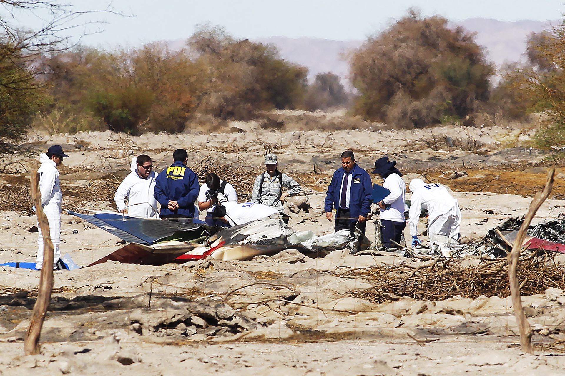Funcionarios de la Policía de Investigaciones (PDI) trabajan en el área donde se accidentó una aeronave de la Fuerza Aérea de Chile (FACH) en Pozo Almonte