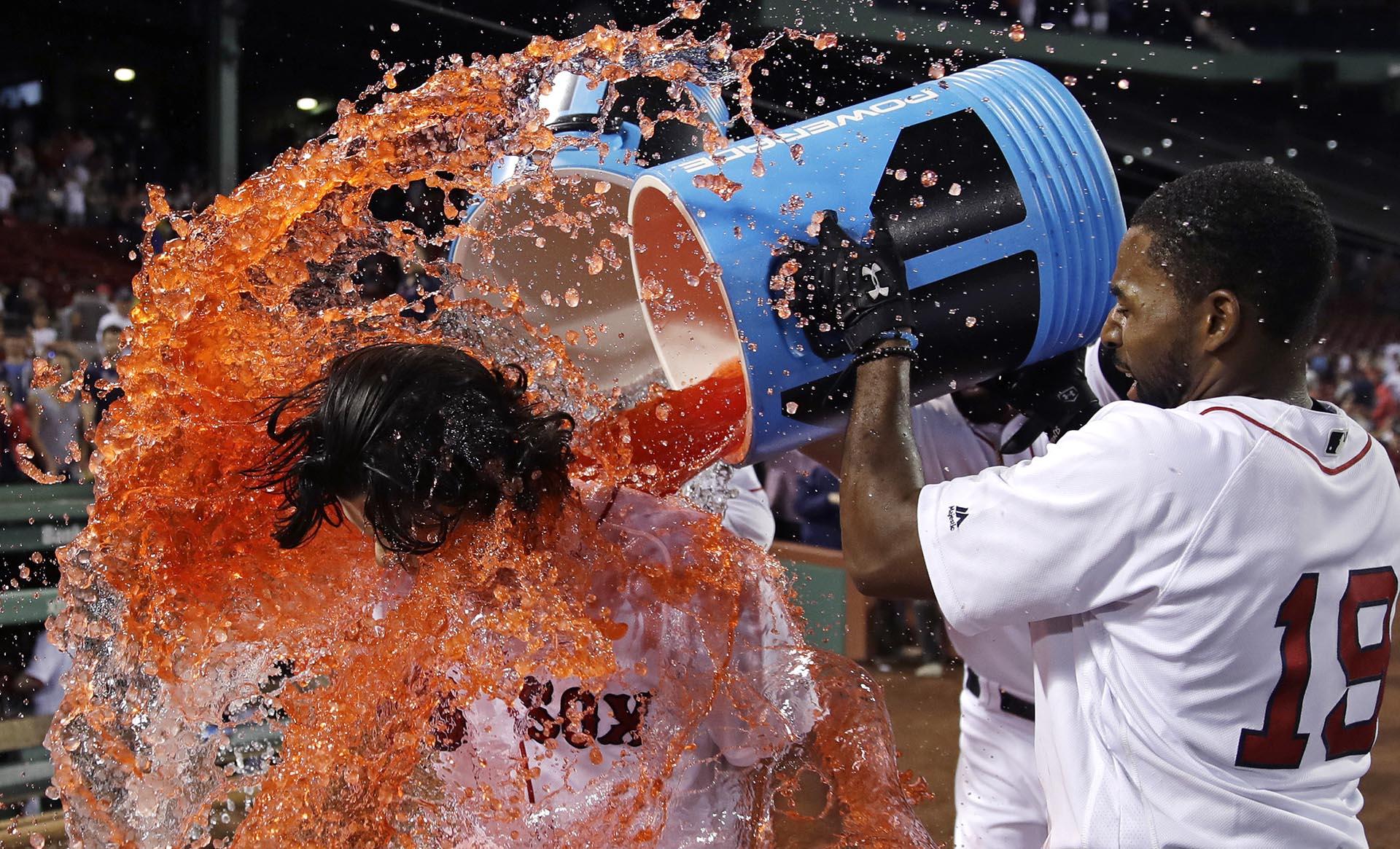 Andrew Benintendi, de Boston Red Sox, es sorprendido por Jackie Bradley Jr. en el partido de béisbol contra los Phillies de Filadelfia en Fenway Park en Boston
