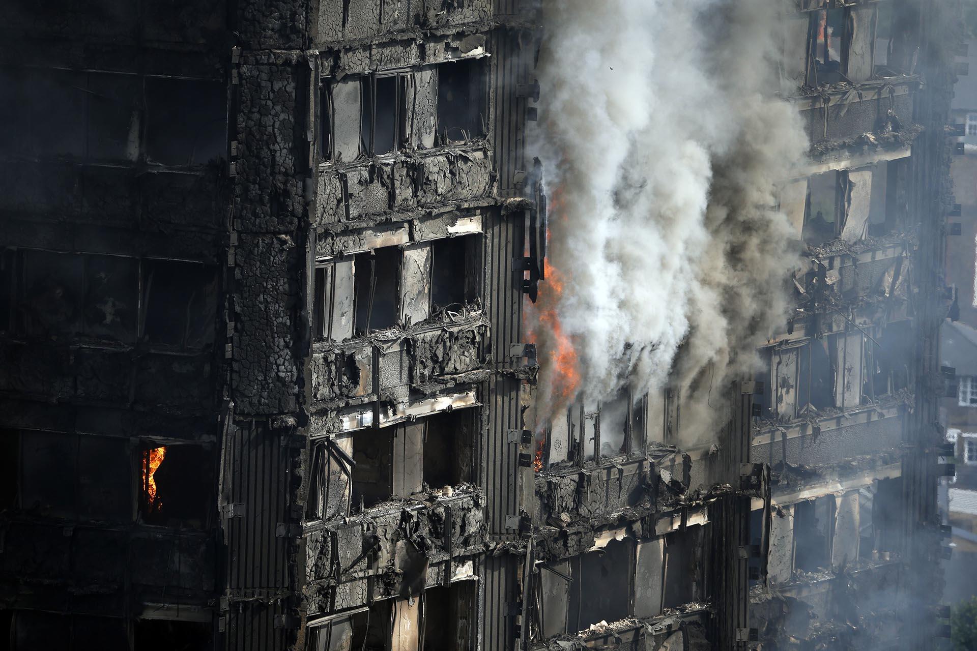 Partes del edificio todavía quemándose horas después del comienzo del incendio mortal en el bloque de apartamentos de gran altura en Londres
