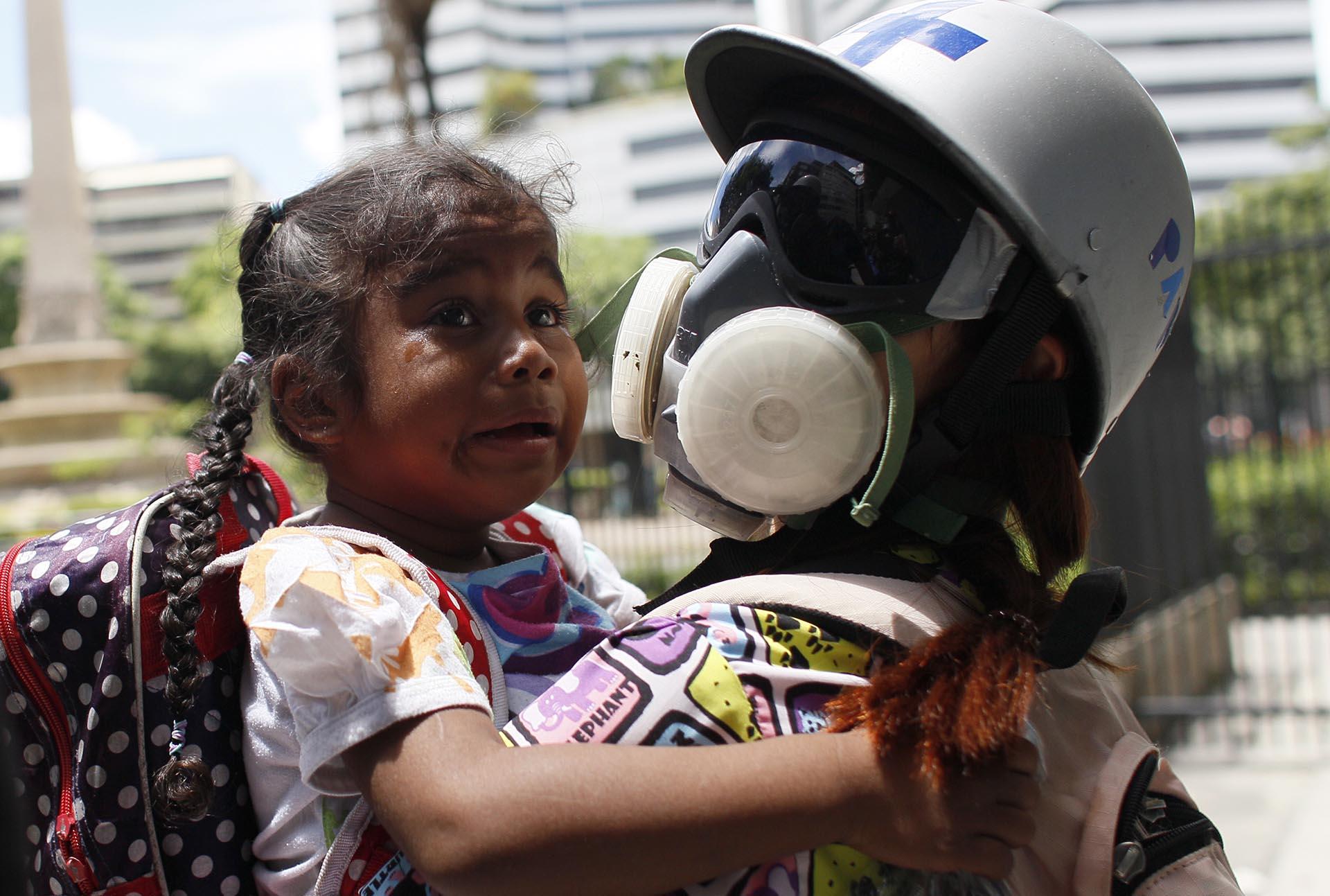 Una paramédica asiste a una niña afectada por gases lacrimógenos durante la represión chavista a una manifestación opositora en Caracas, Venezuela