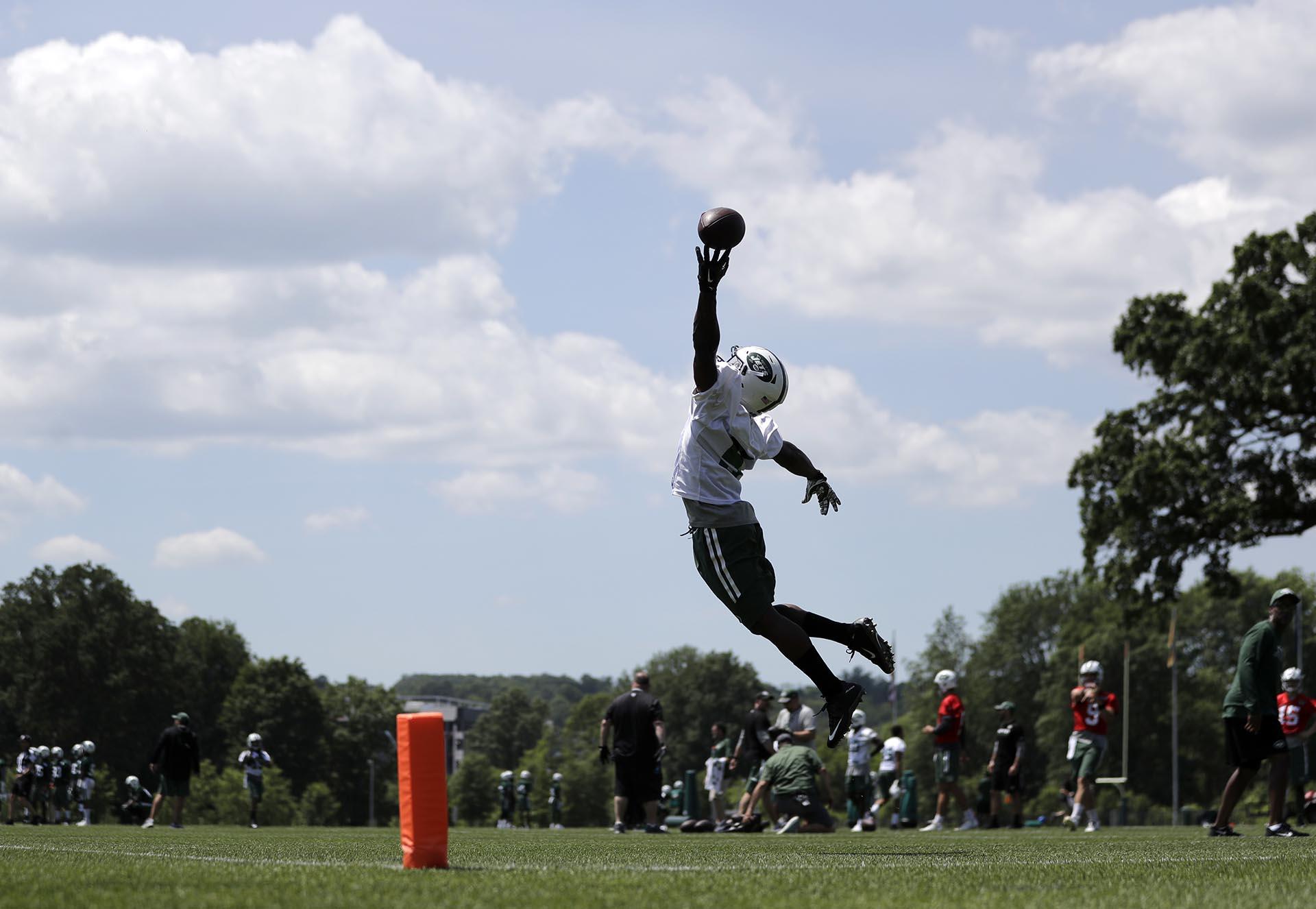 Willie Quinn, de los New York Jets, intenta conseguir un pase de Bryce Petty durante una práctica de la NFL