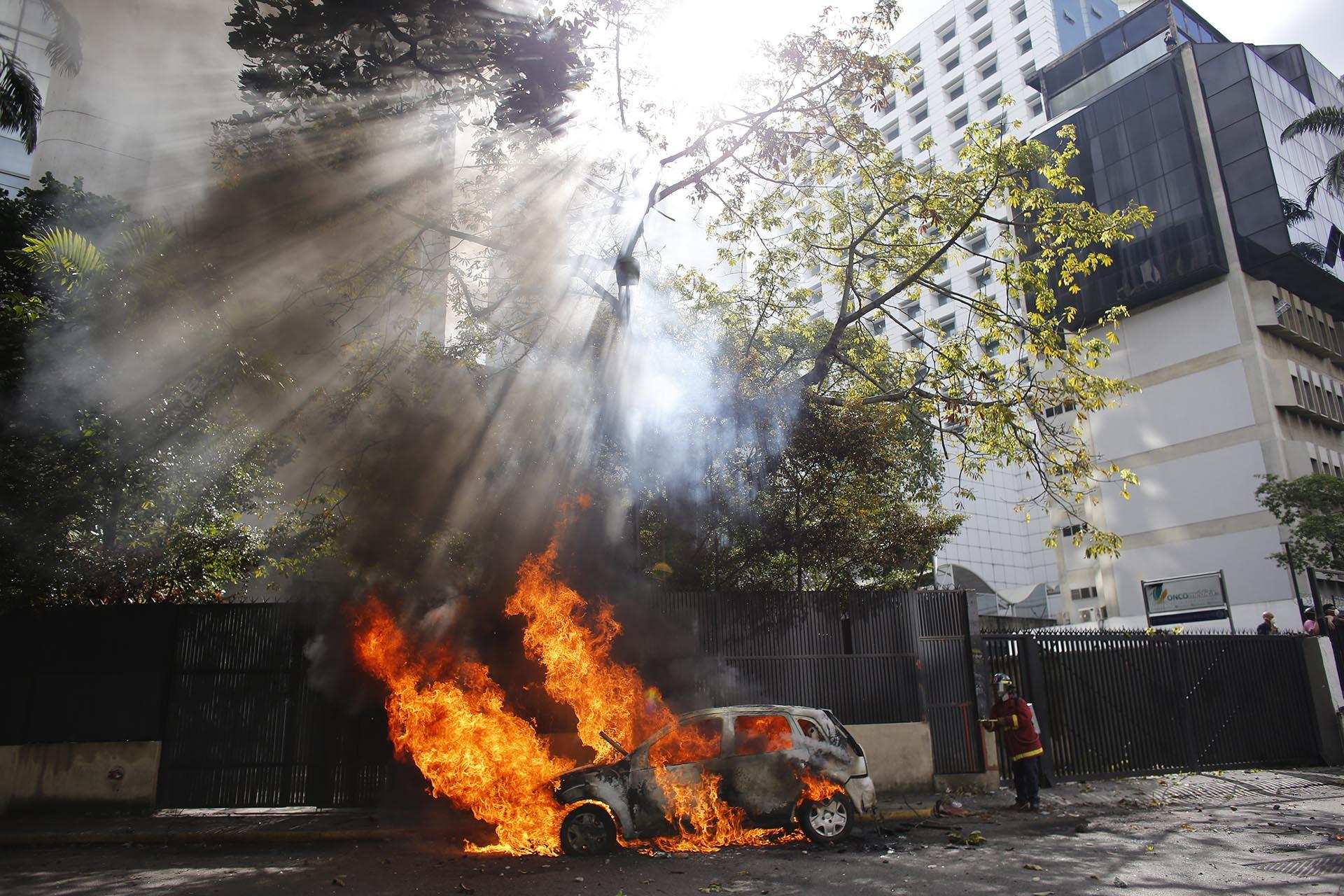 Un bombero apaga el fuego de un coche incendiado durante la represión a las protestas en Caracas, Venezuela