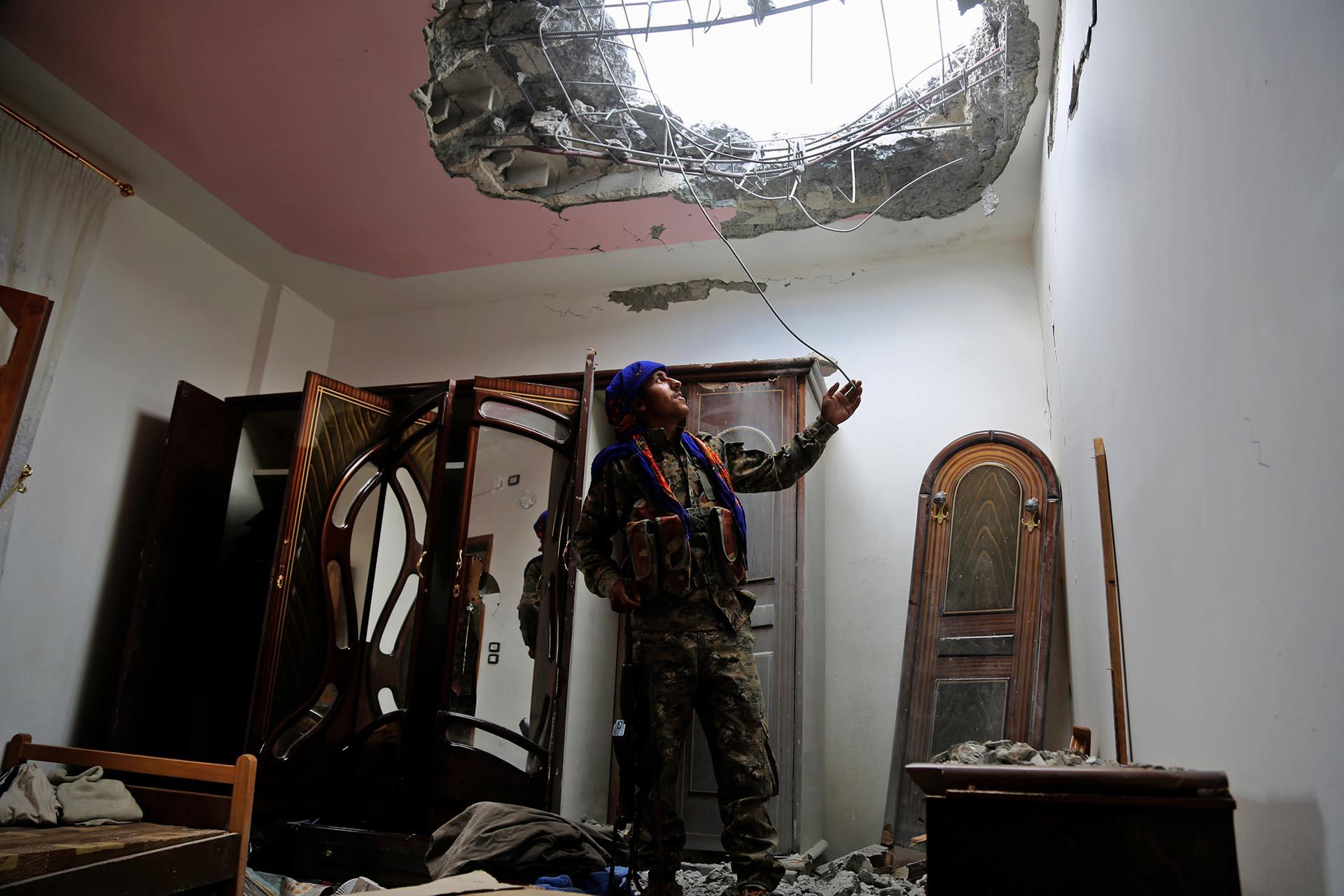 Un miembro de las Fuerzas Democráticas Sirias (SDF), formadas por una alianza de combatientes árabes y kurdos, examina los daños en un barrio del frente oriental de Raqqa, bastión sirio del grupo ISIS, después de sacar del área a los yihadistas en junio