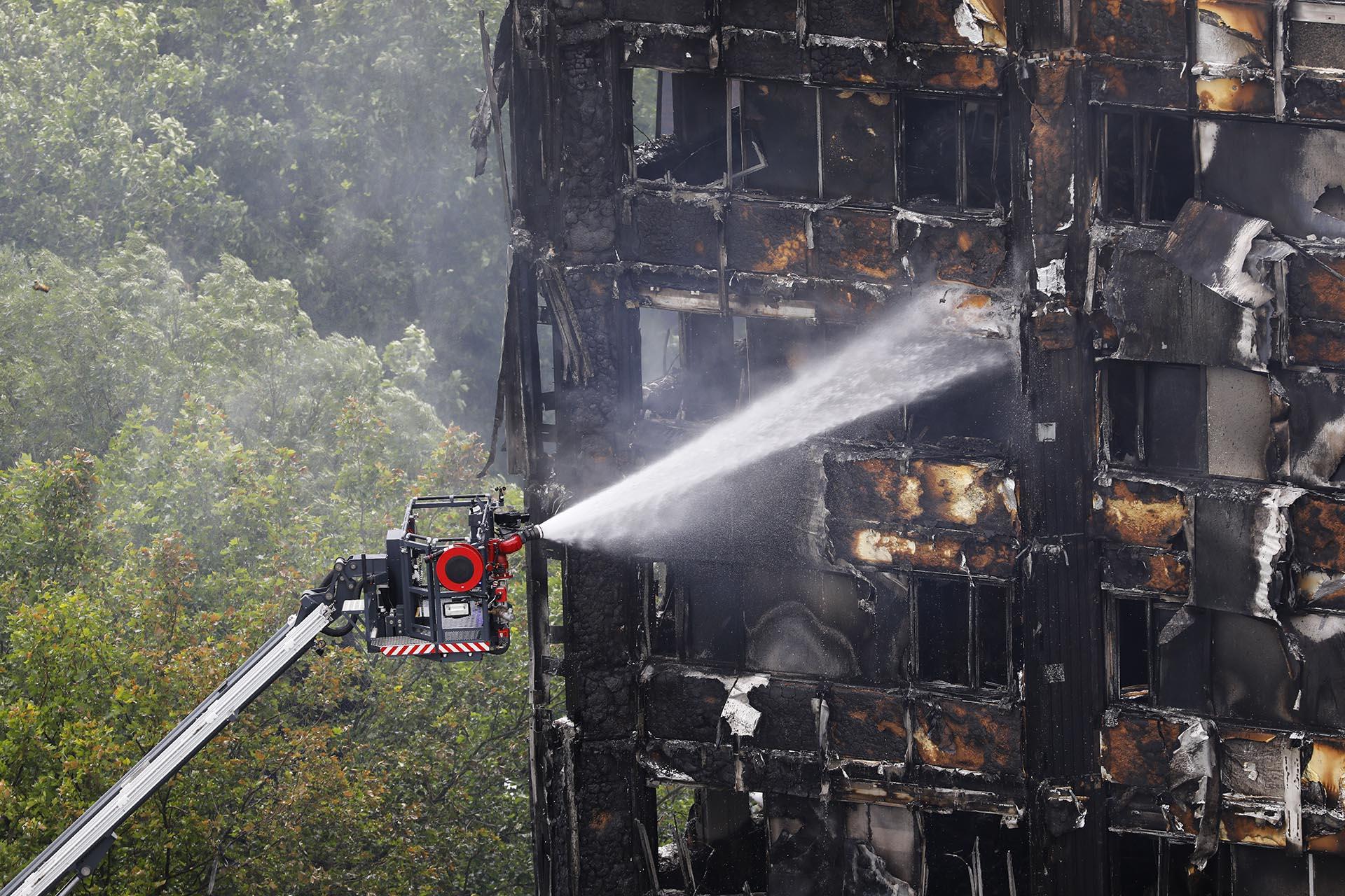 Una manguera automatizada rocía el agua sobre la incendiada torre Grenfell en Londres