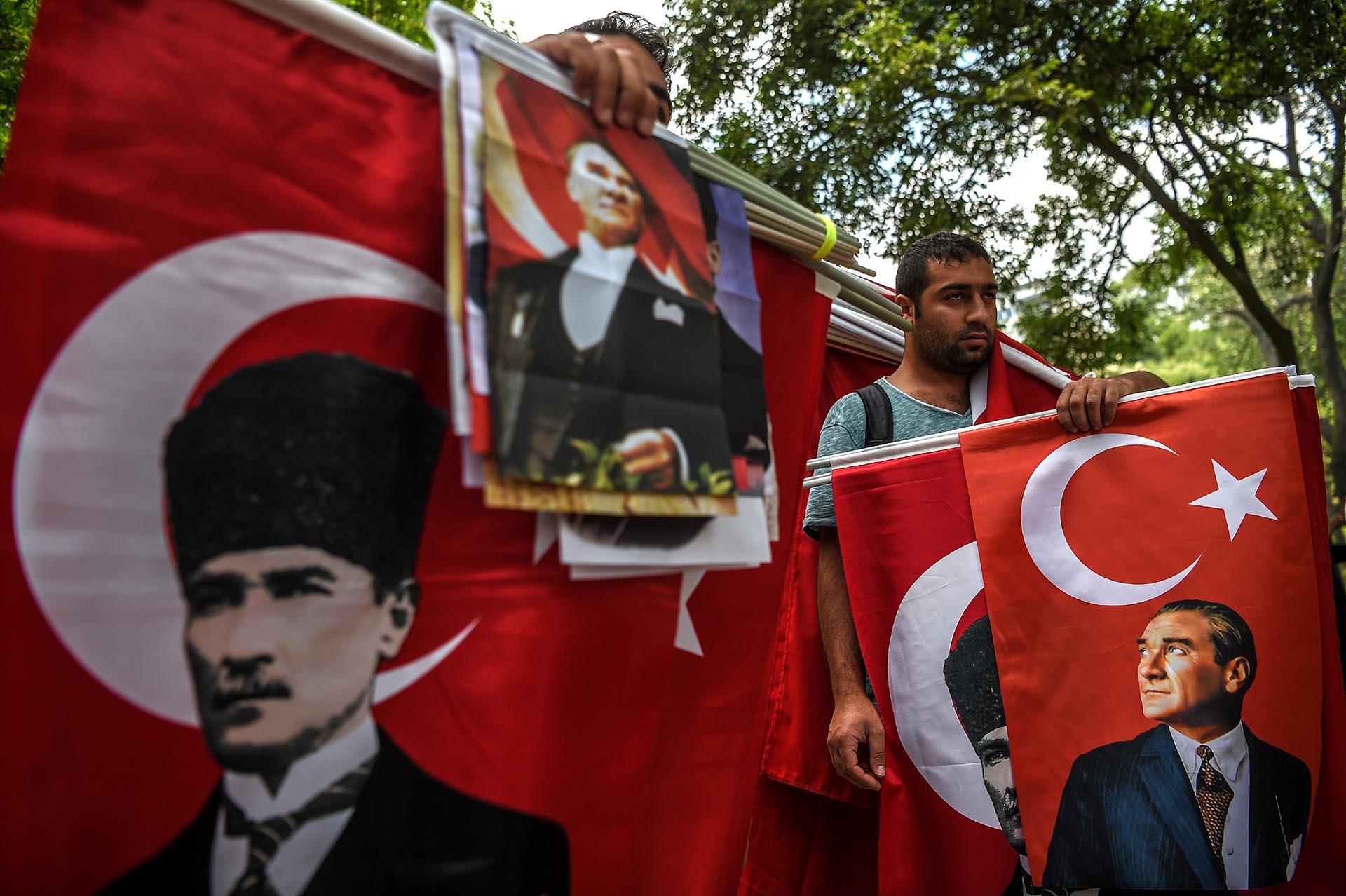 Vendedores de banderas en Estambul sostienen los retratos de Mustafa Kemal Ataturk, fundador de la Turquía moderna, durante una demostración de seguidores del principal partido de la oposición de Turquía para protestar por el encarcelamiento de uno de sus diputados