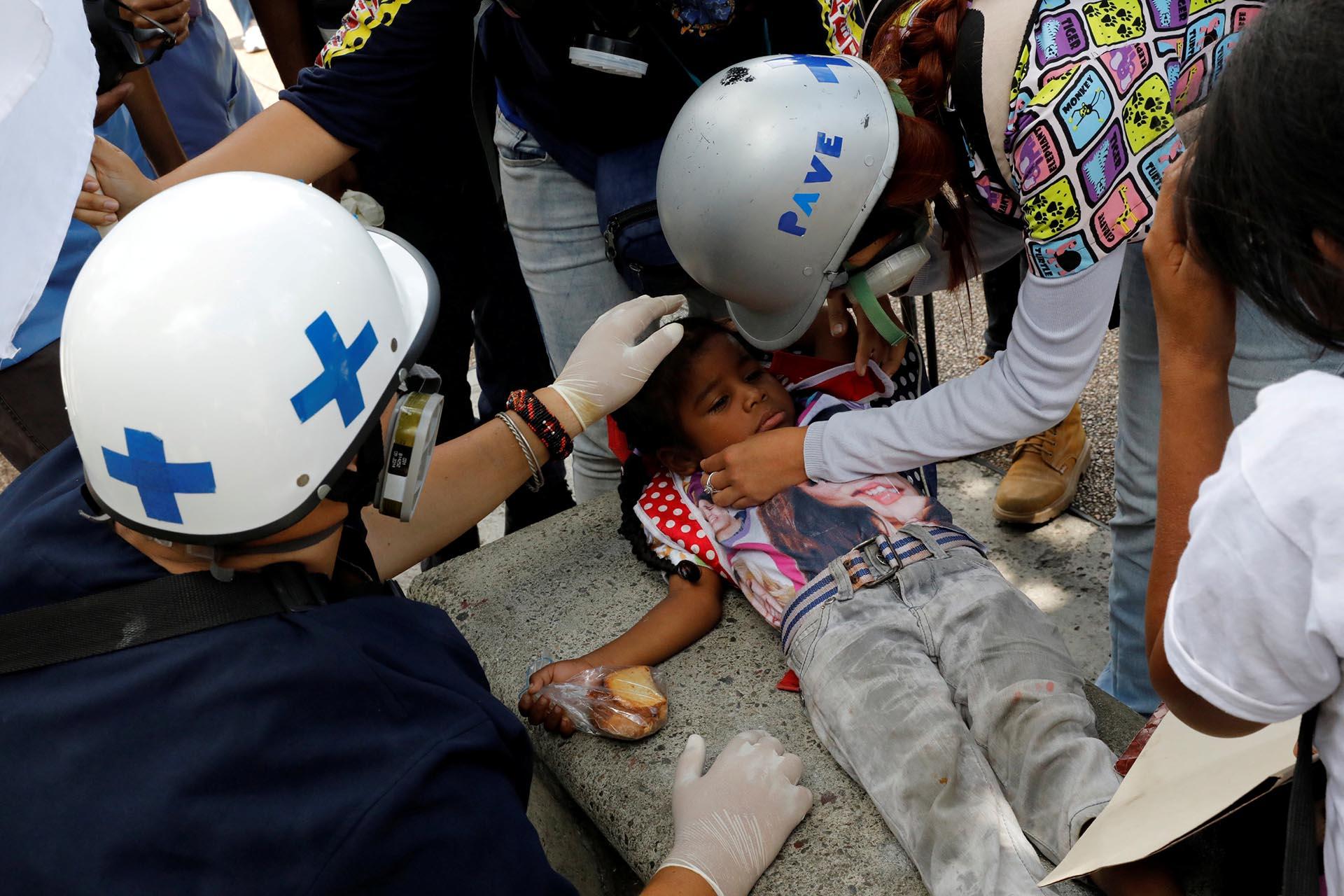 Un niño afectado por gases lacrimógenos es asistido por miembros voluntarios de un equipo de atención primaria durante una manifestación contra el gobierno del presidente de Venezuela, Nicolás Maduro, en Caracas