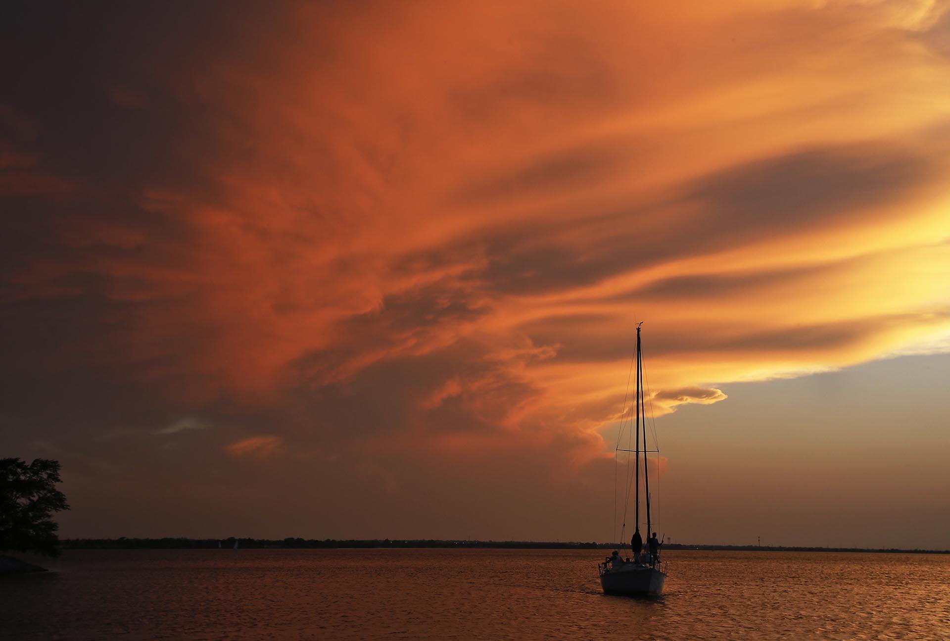 Un barco vuelve al puerto cuando el sol se pone en el lago Hefner en Oklahoma City