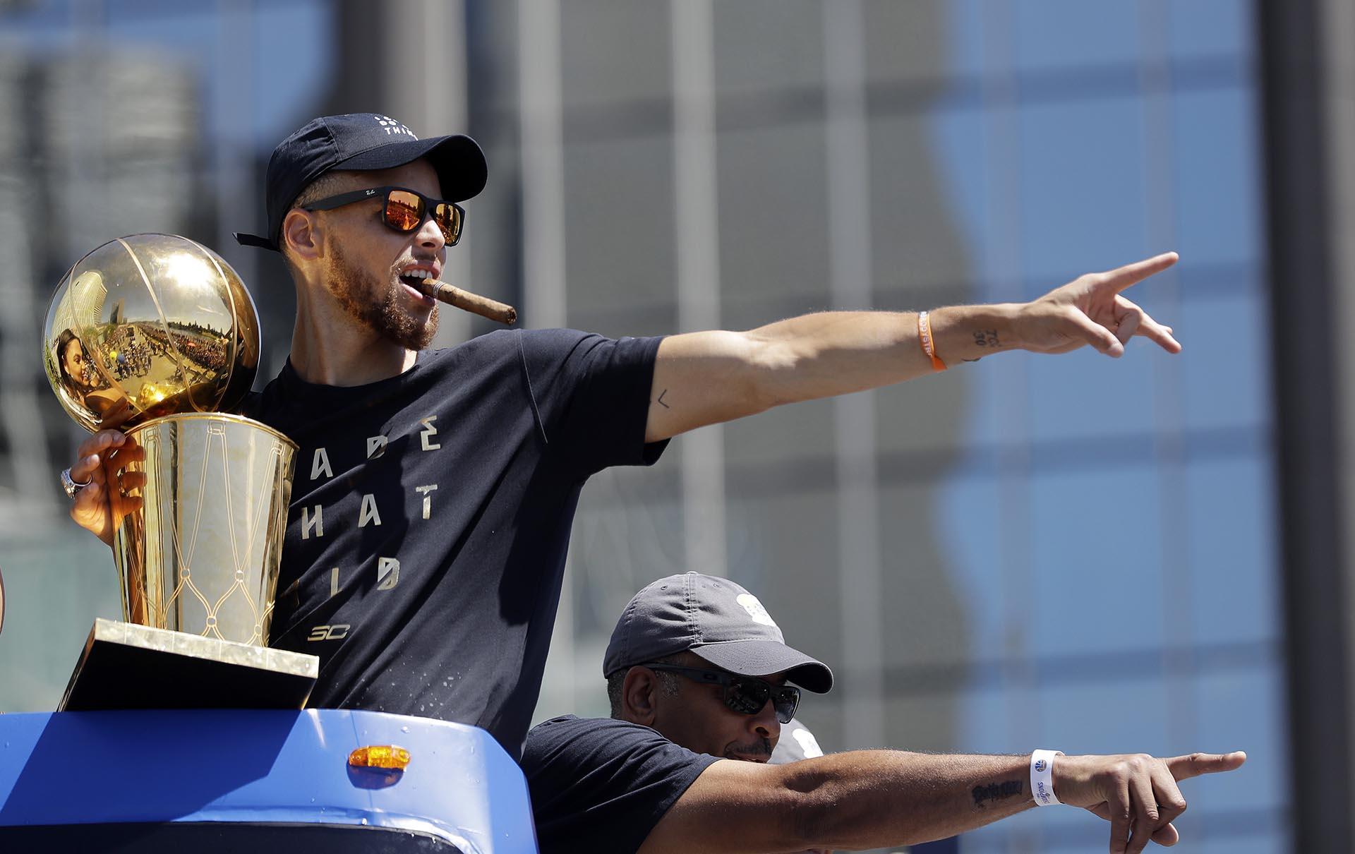 Stephen Curry, de Golden State Warriors, y su padre Dell durante un desfile para celebrar el campeonato de baloncesto de la NBA