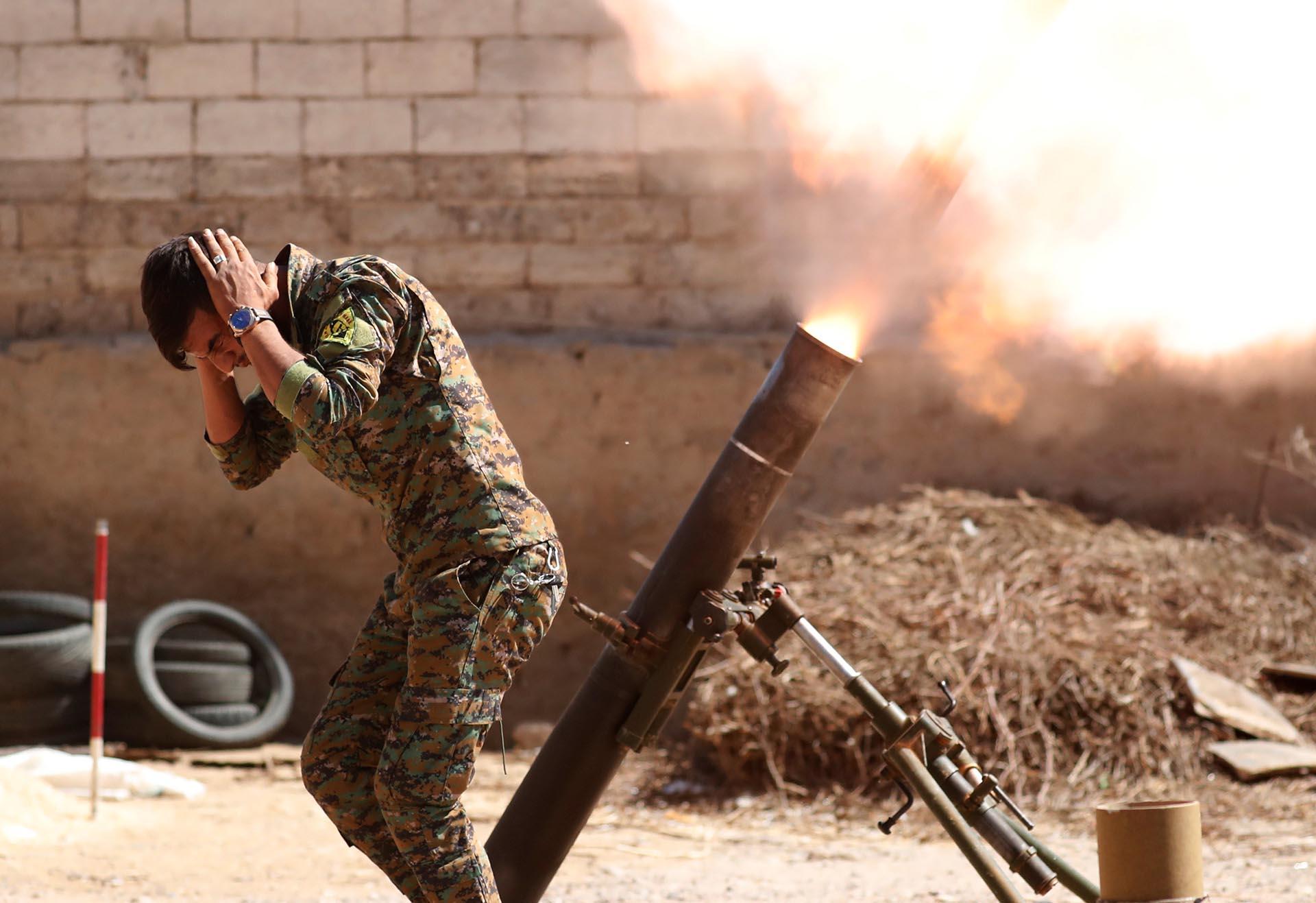 Un combatiente kurdo de las Unidades de Protección del Pueblo (YPG) dispara una ronda de mortero de 120 mm en Raqqa, Siria