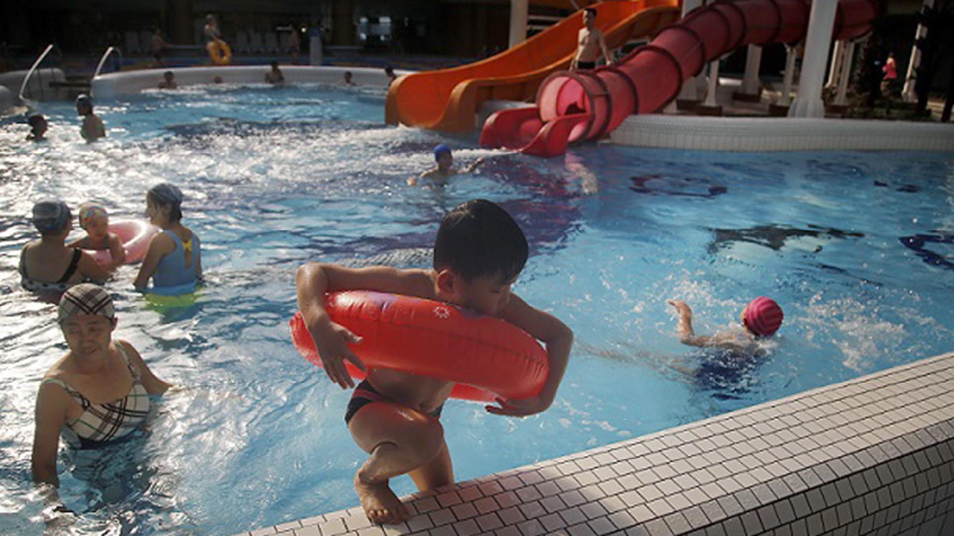 Un niño saliendo de la piscina de la parte interior del parque acuático Munsu, abierto para locales y extranjeros (AP)