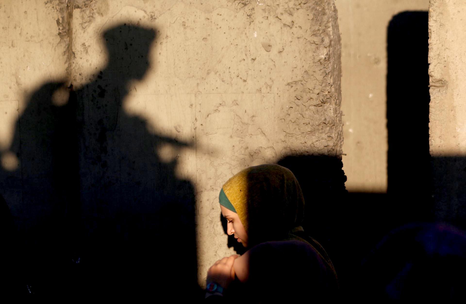 Una mujer palestina se abre camino a través del puesto de control de Qalandia en Israel para asistir a la oración del viernes del mes sagrado del ayuno del Ramadán en la mezquita de Jerusalén