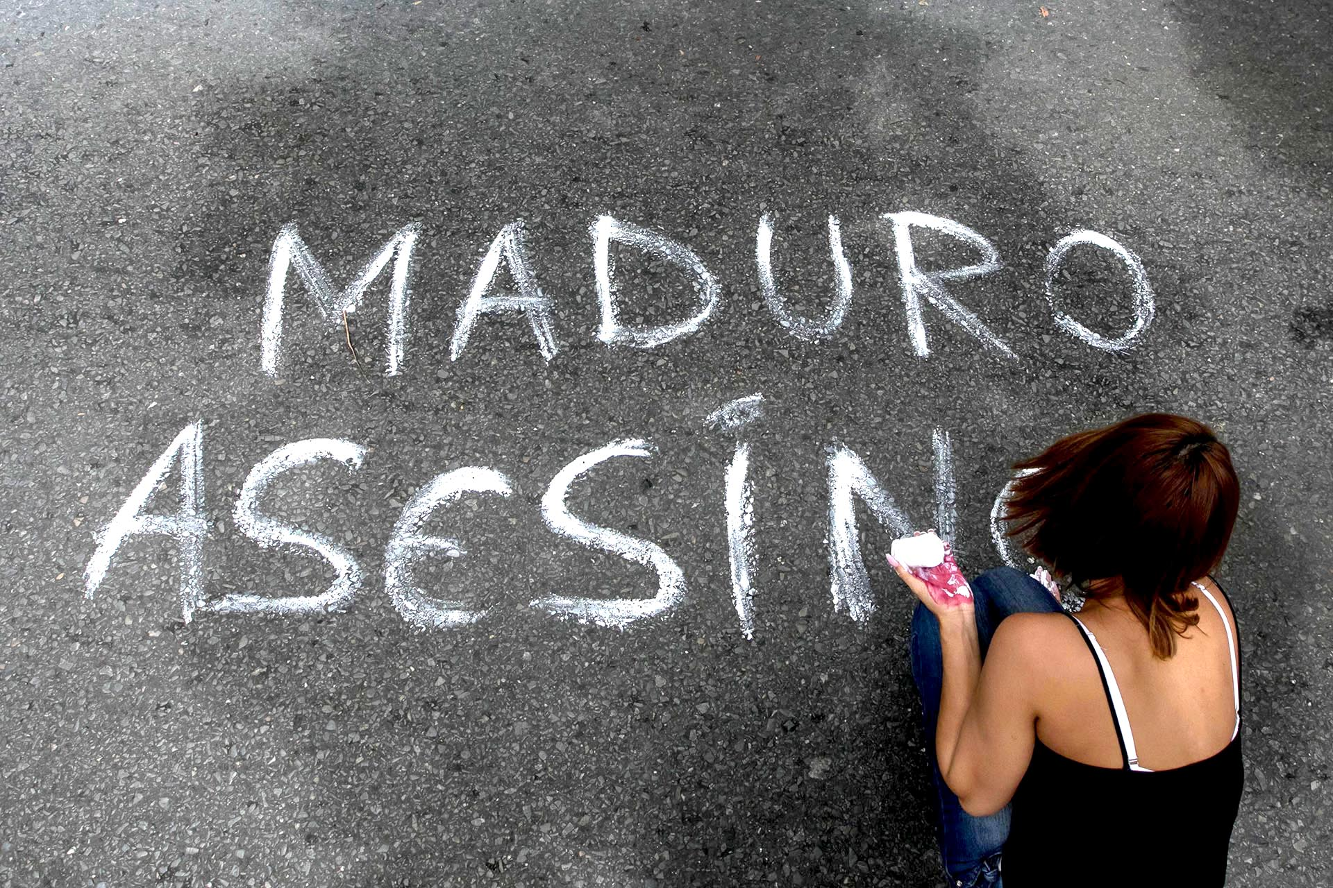 Una mujer escribe un mensaje sobre el asfalto durante una manifestación en Caracas