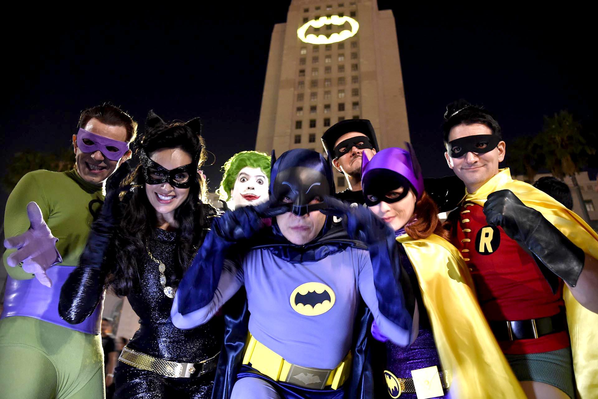 """Fanáticos de Batman vestidos como los personajes de la serie frente a una """"Batiseñal"""" proyectada en el Ayuntamiento de Los Ángeles durante un homenaje al fallecido actor Adam West"""