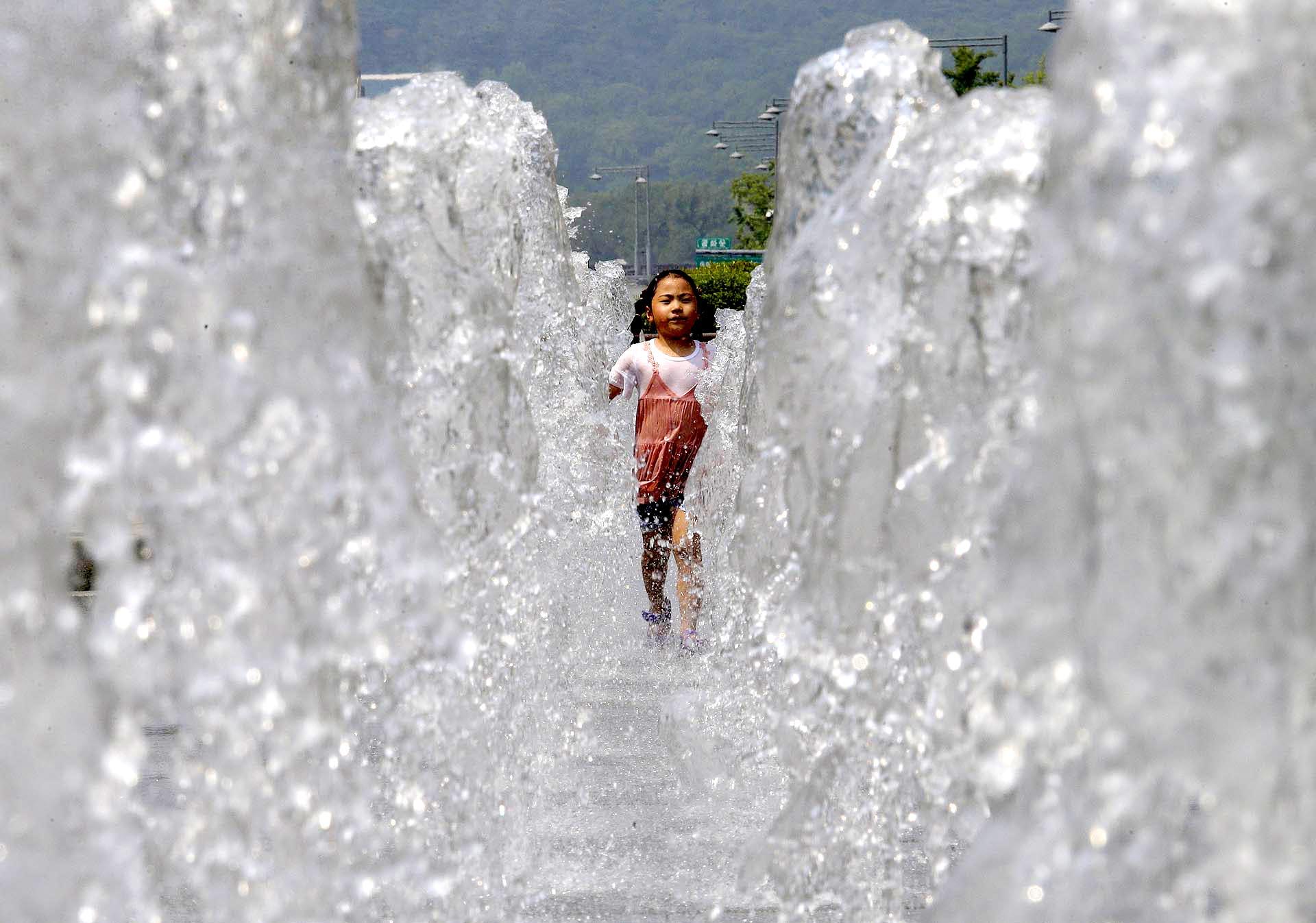 Una niña corre a través de una fuente de agua pública para refrescarse en Seúl, Corea del Sur