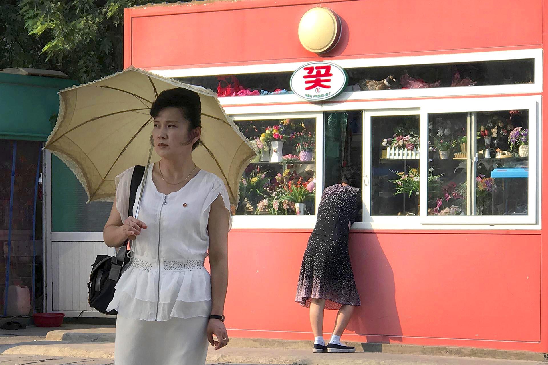 Una mujer se detiene en un quiosco que vende regalos y flores en Pyongyang, Corea del Norte, mientras otra espera a cruzar la calle