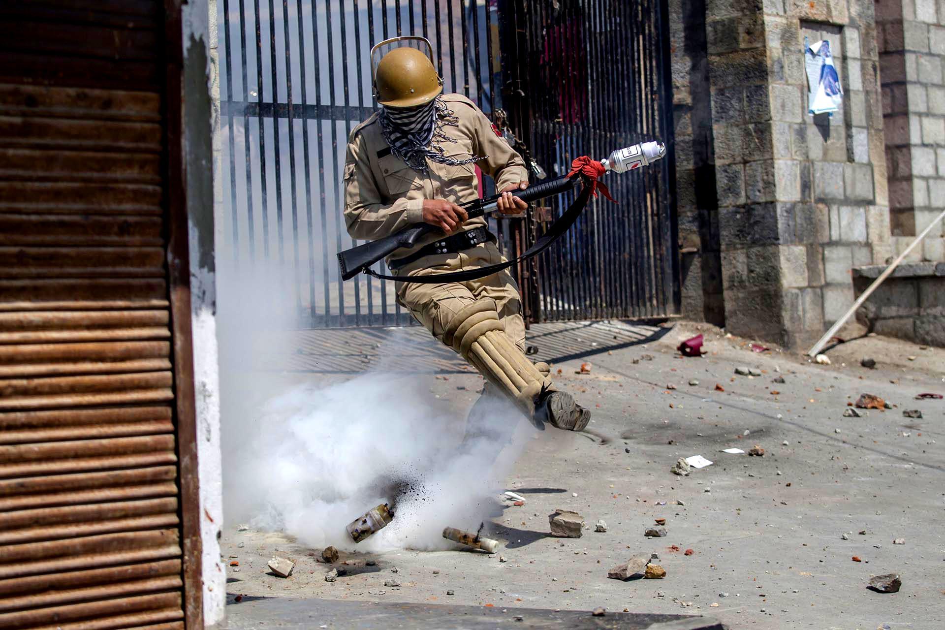 Un policía indio patea un proyectil de gas lacrimógeno en un intento de arrojarlo hacia los manifestantes en Srinagar, en el valle de Cachemira, controlado por la India