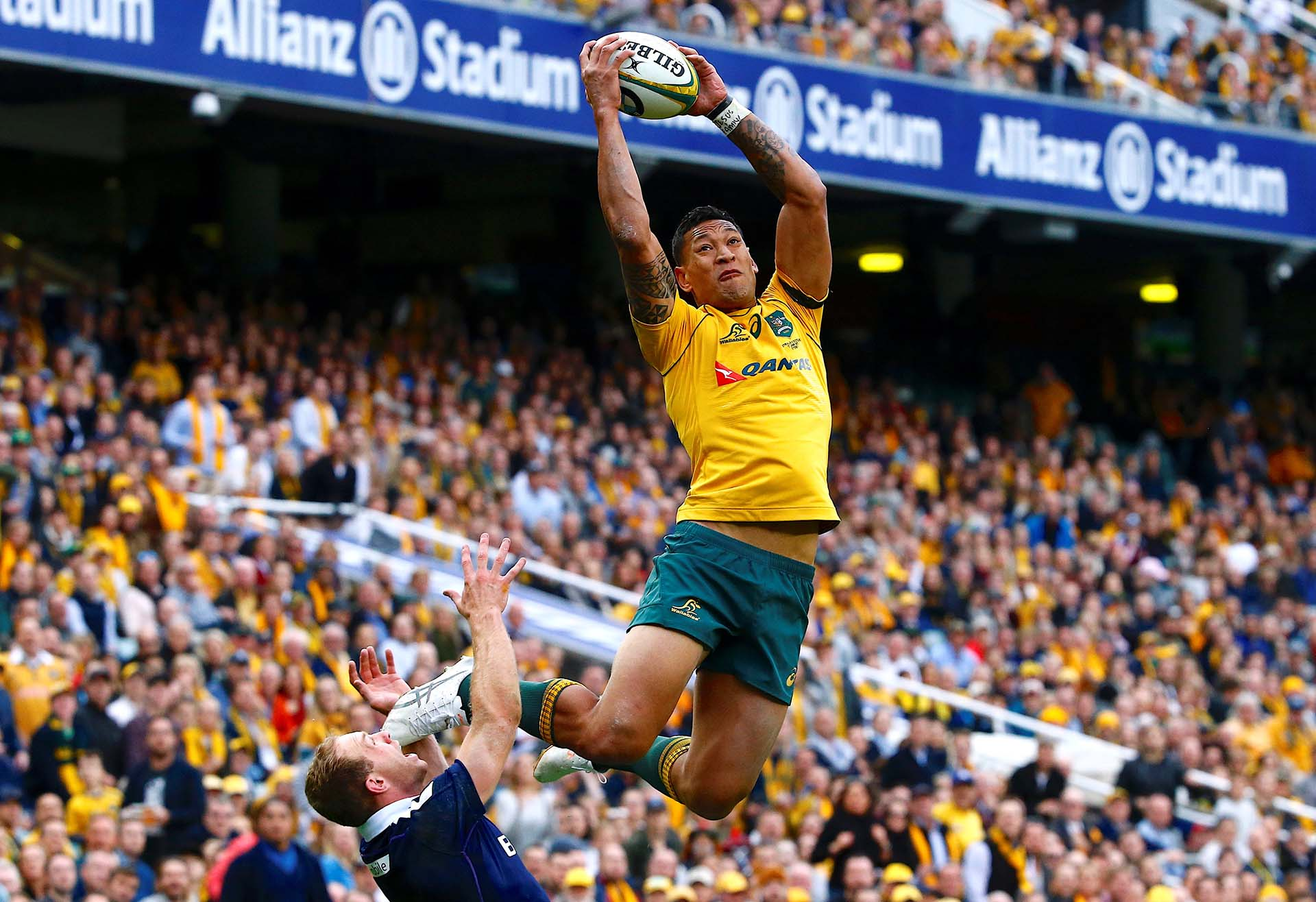 El australiano Israel Folau salta por encima del escocés Greig Tonks para tomarr el balón y marcar un try en Sydney
